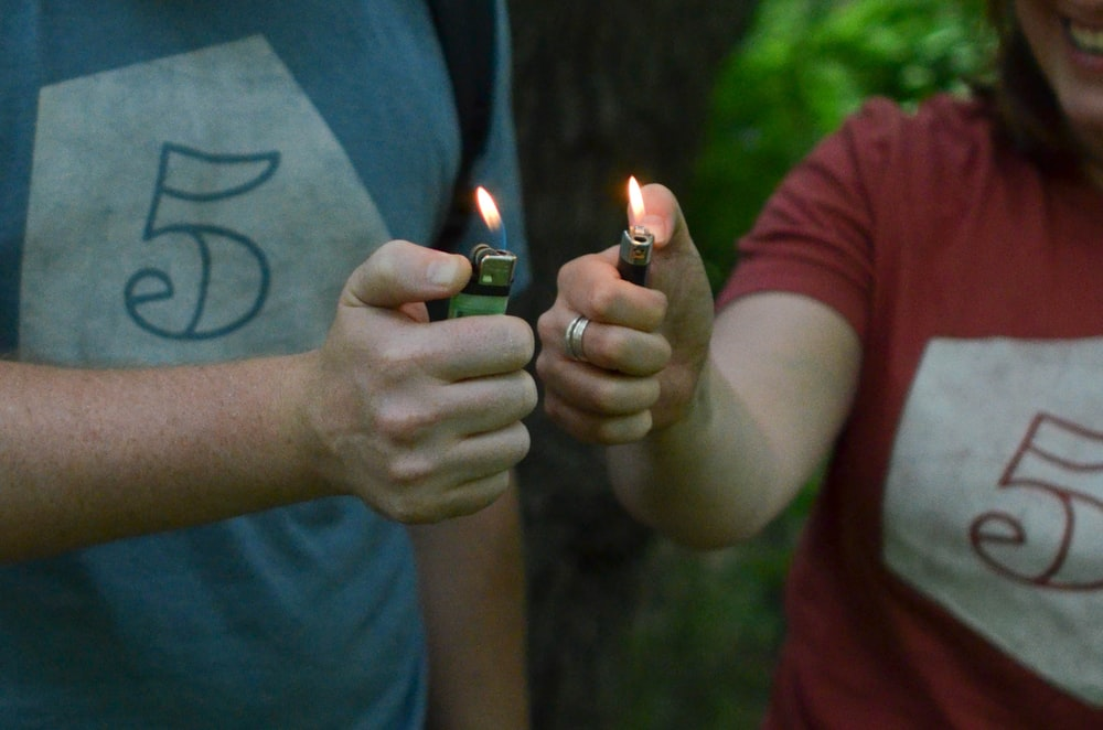 man and woman lit the two lighters they are holding