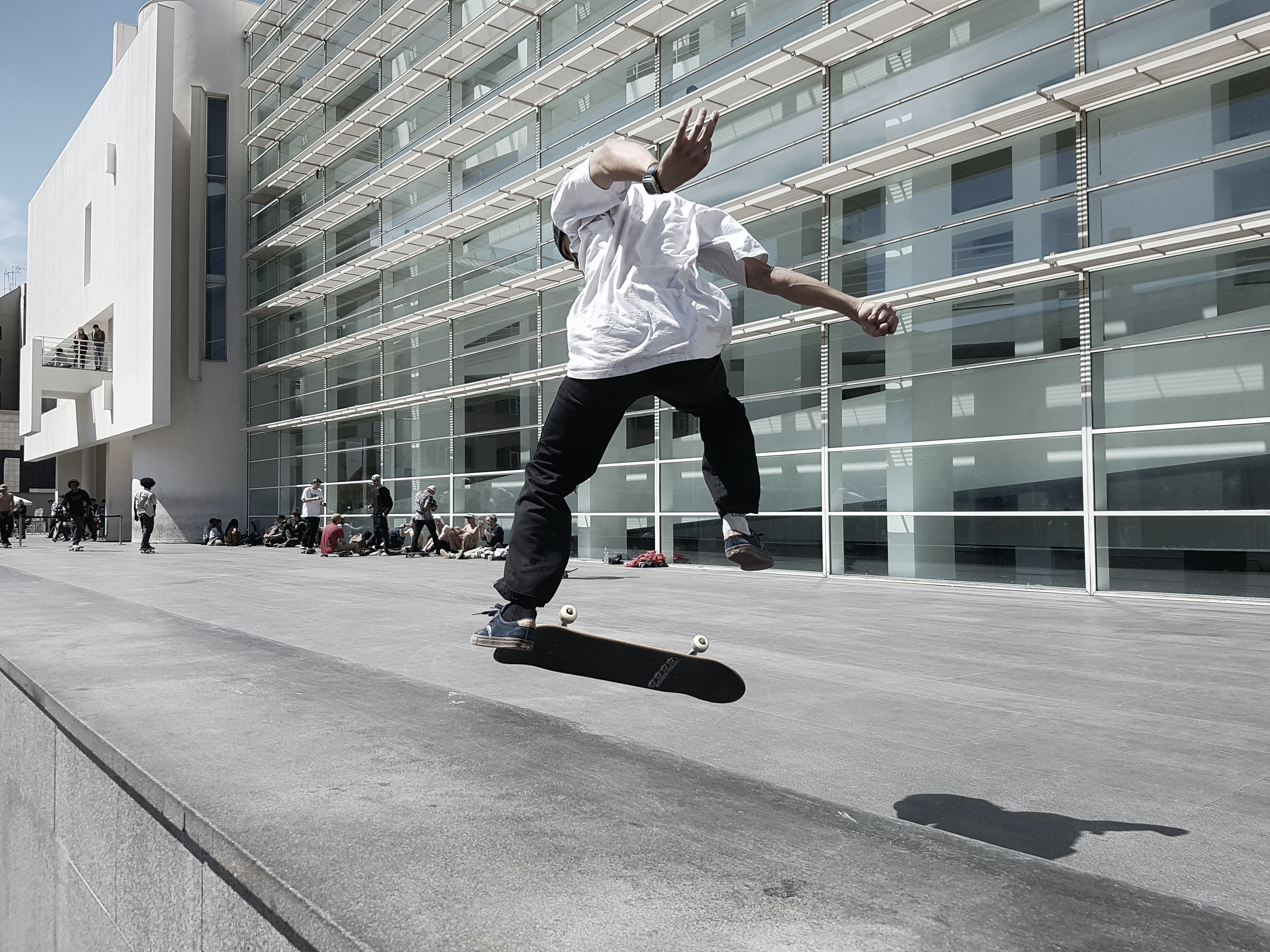 Skater performing trick on concrete pavement during daytime outside Barcelona Museum of Contemporary Art