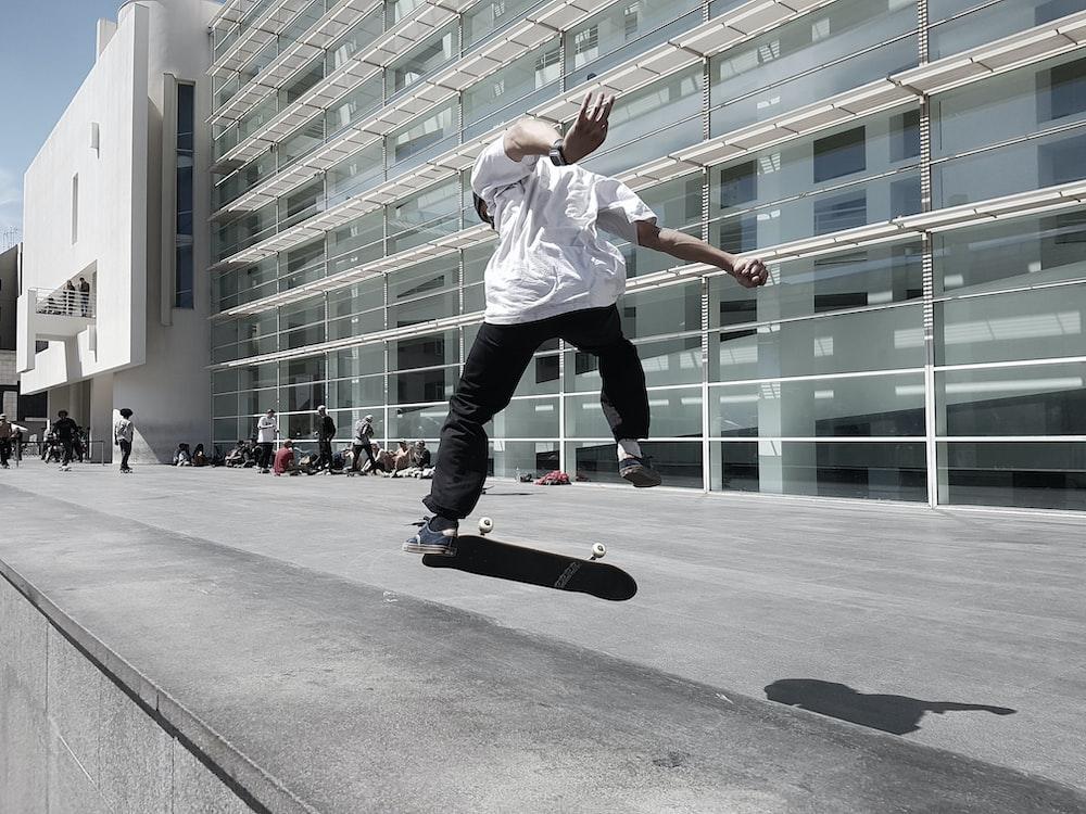 man skateboarding beside building during daytime