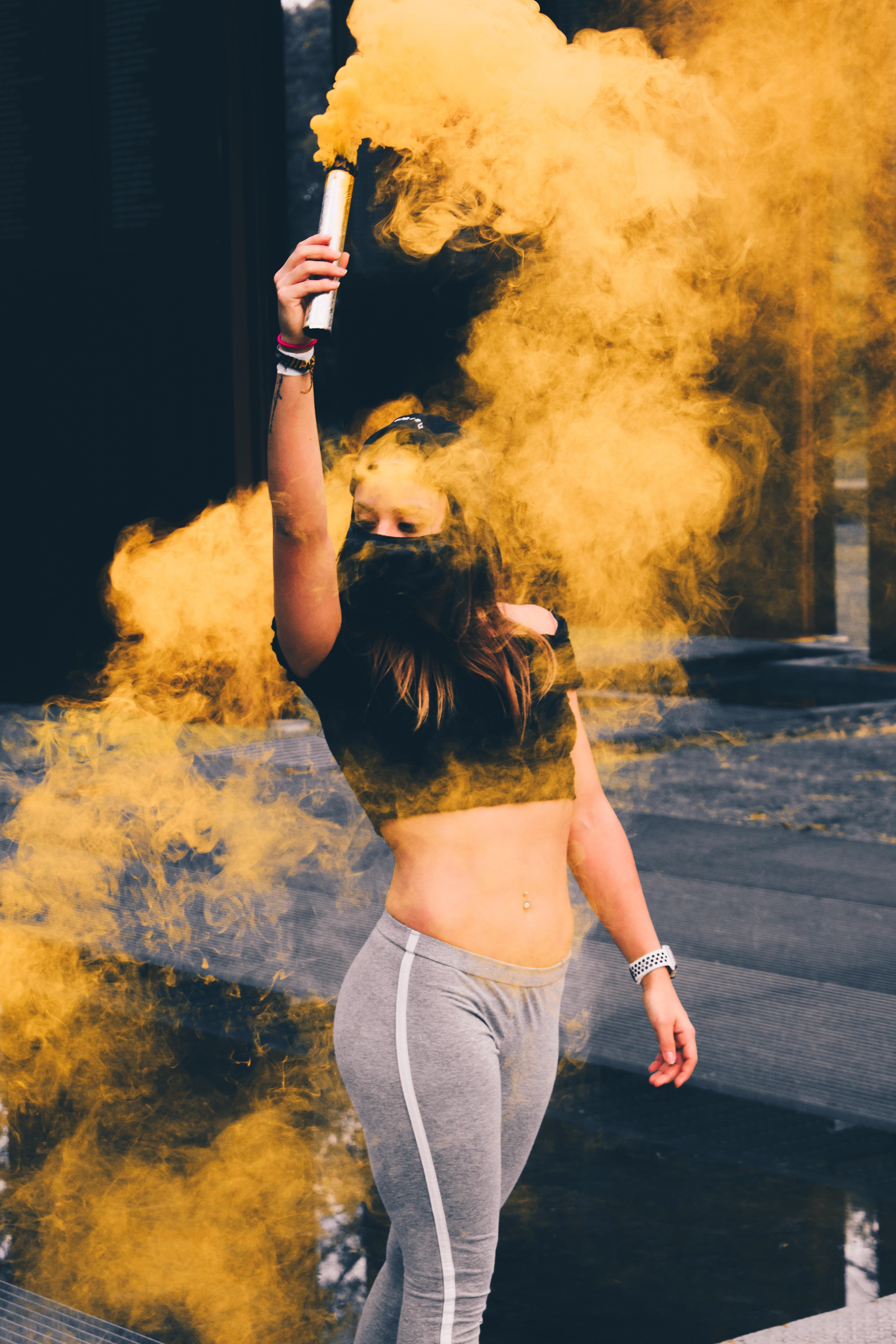 macro photography of woman wearing mask while raising smoke bomb