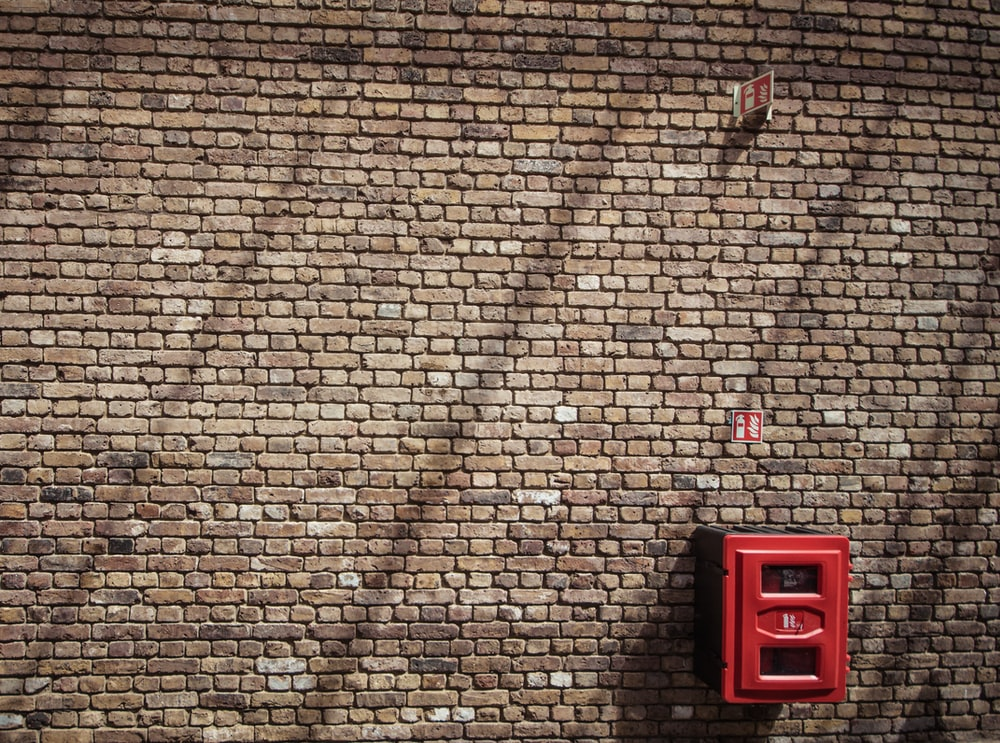 red metal case mounted on bricked wall