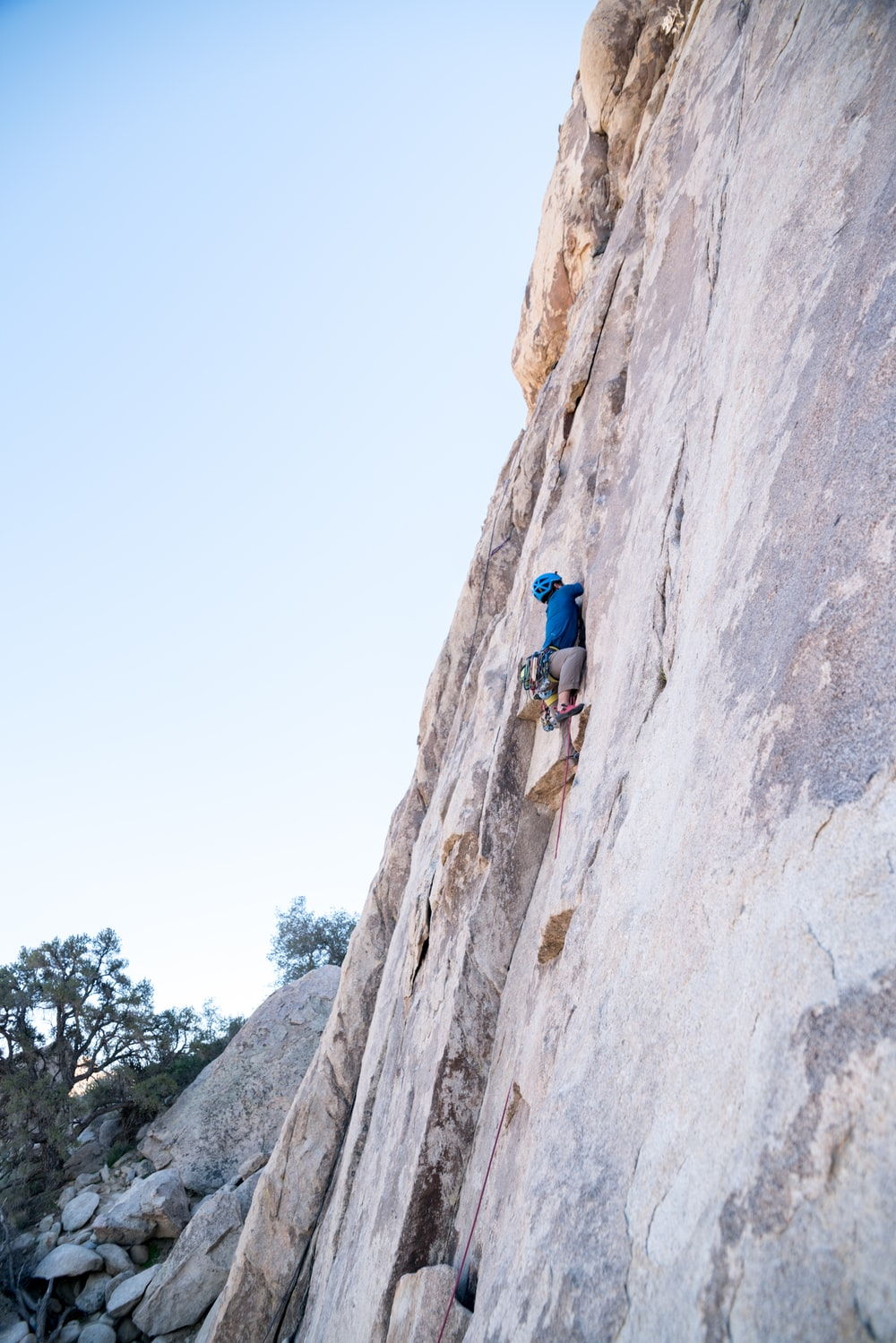 person rock climbing on rocky mountain wall during daytime