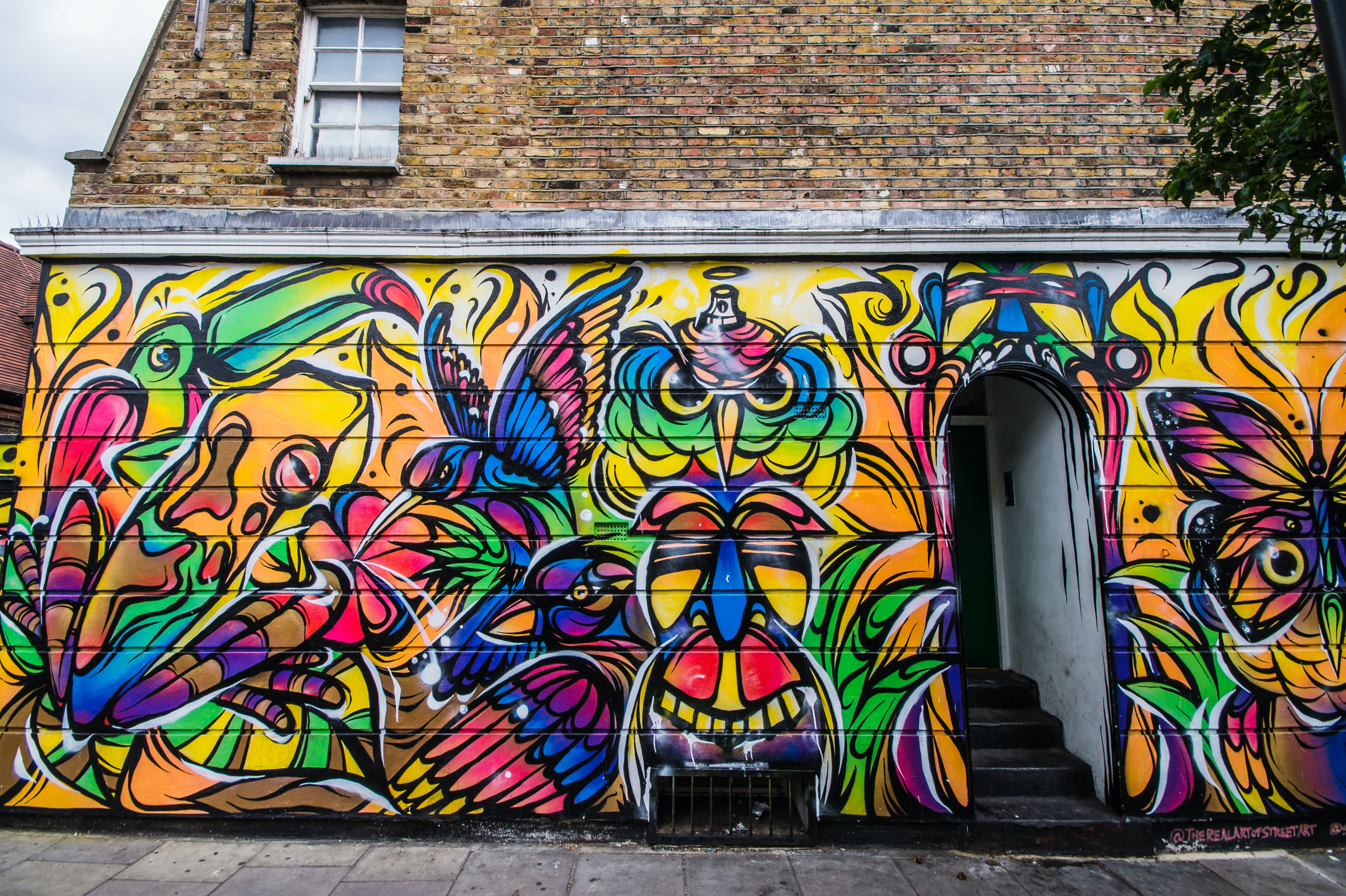 Colorful street art graffiti painting on building exterior in Camden Town