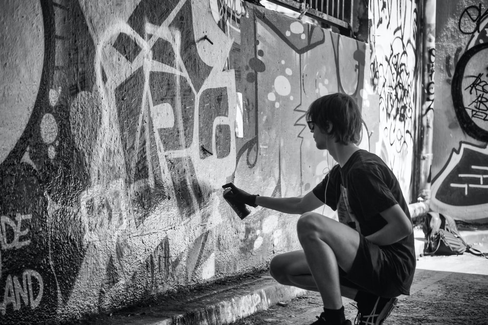 Black and white photo of an artist spray painting graffiti on a wall on leake street
