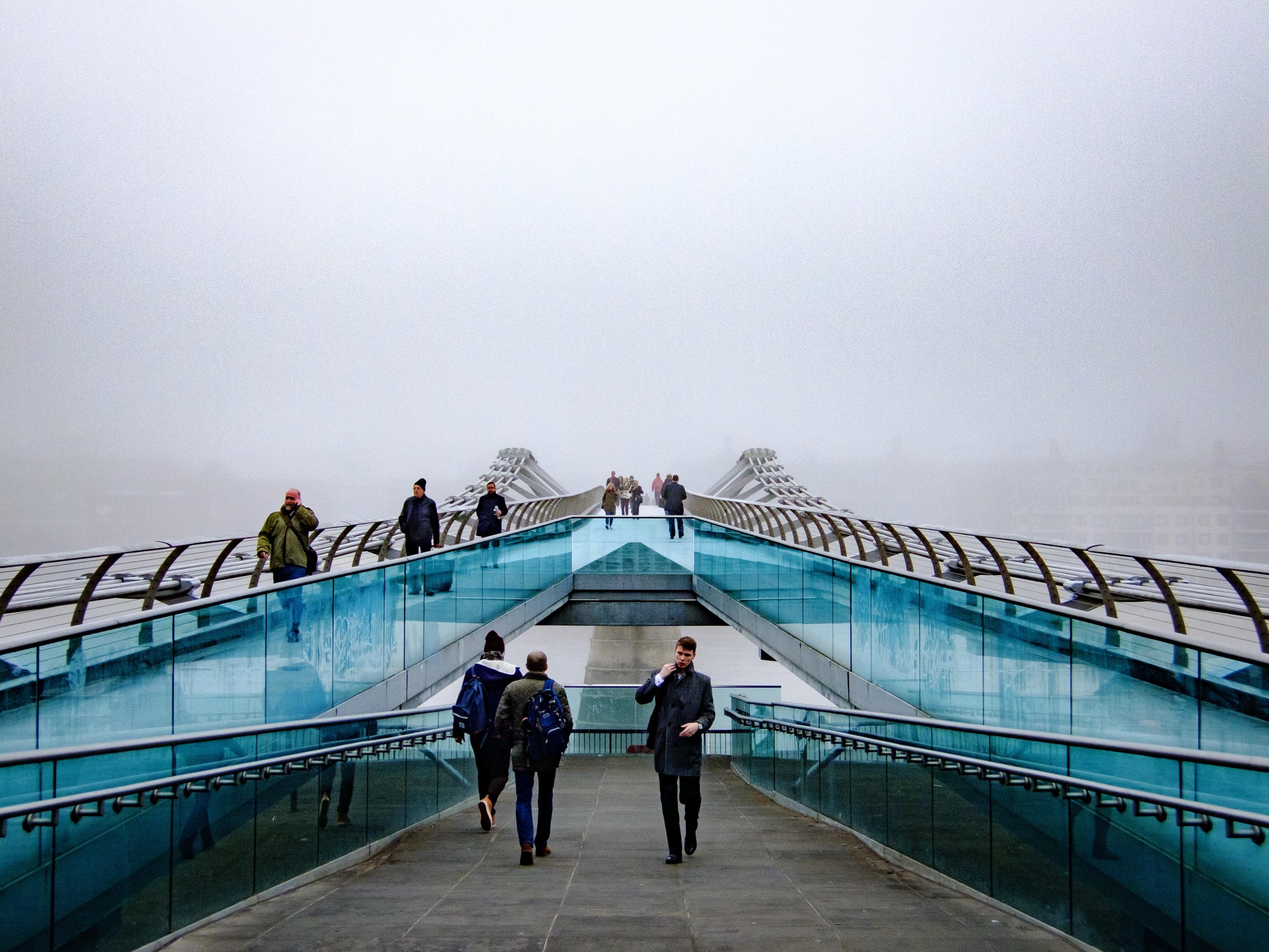 people walking near glass railings