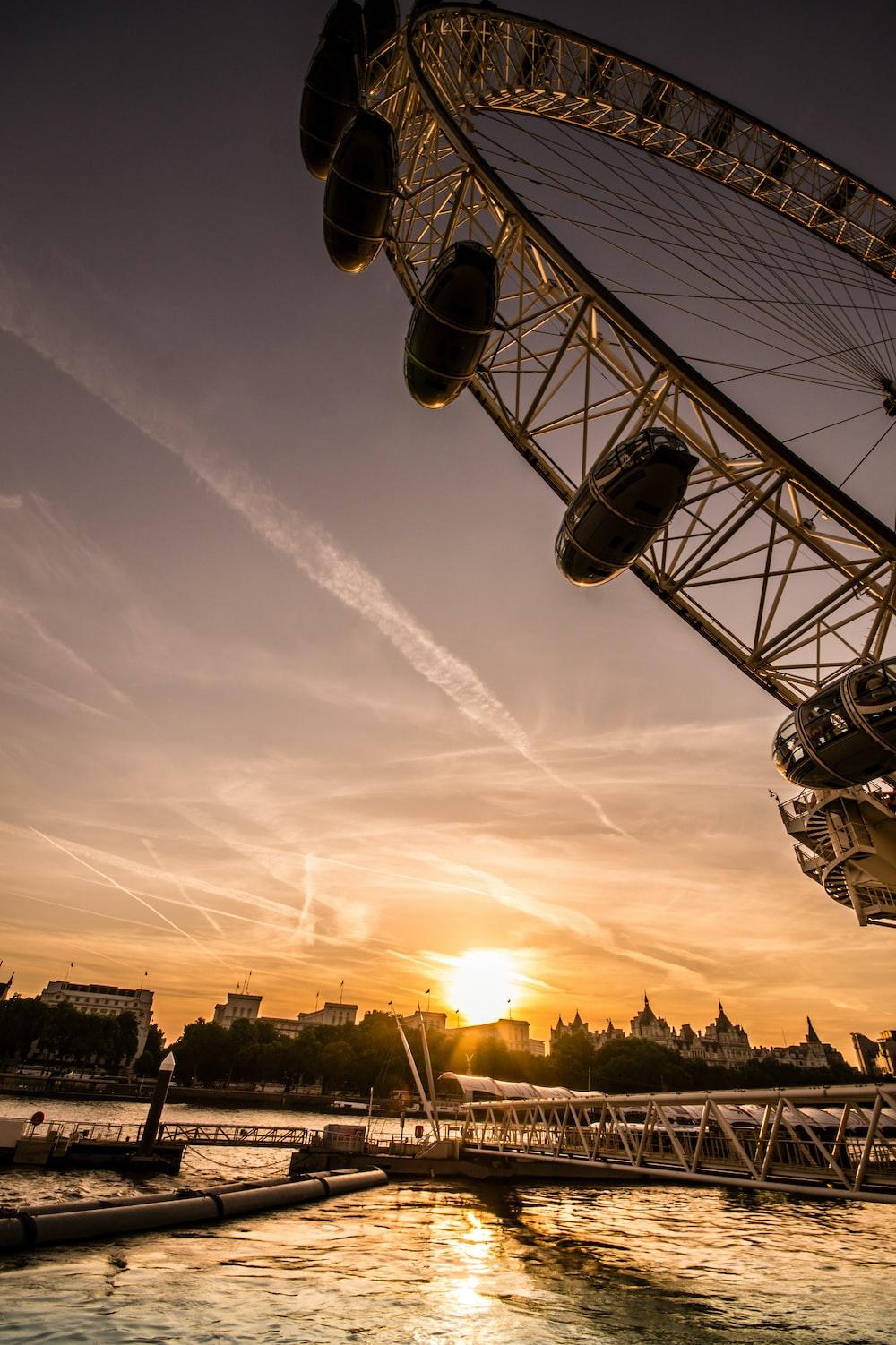 ferris wheel near bridge at golden hour