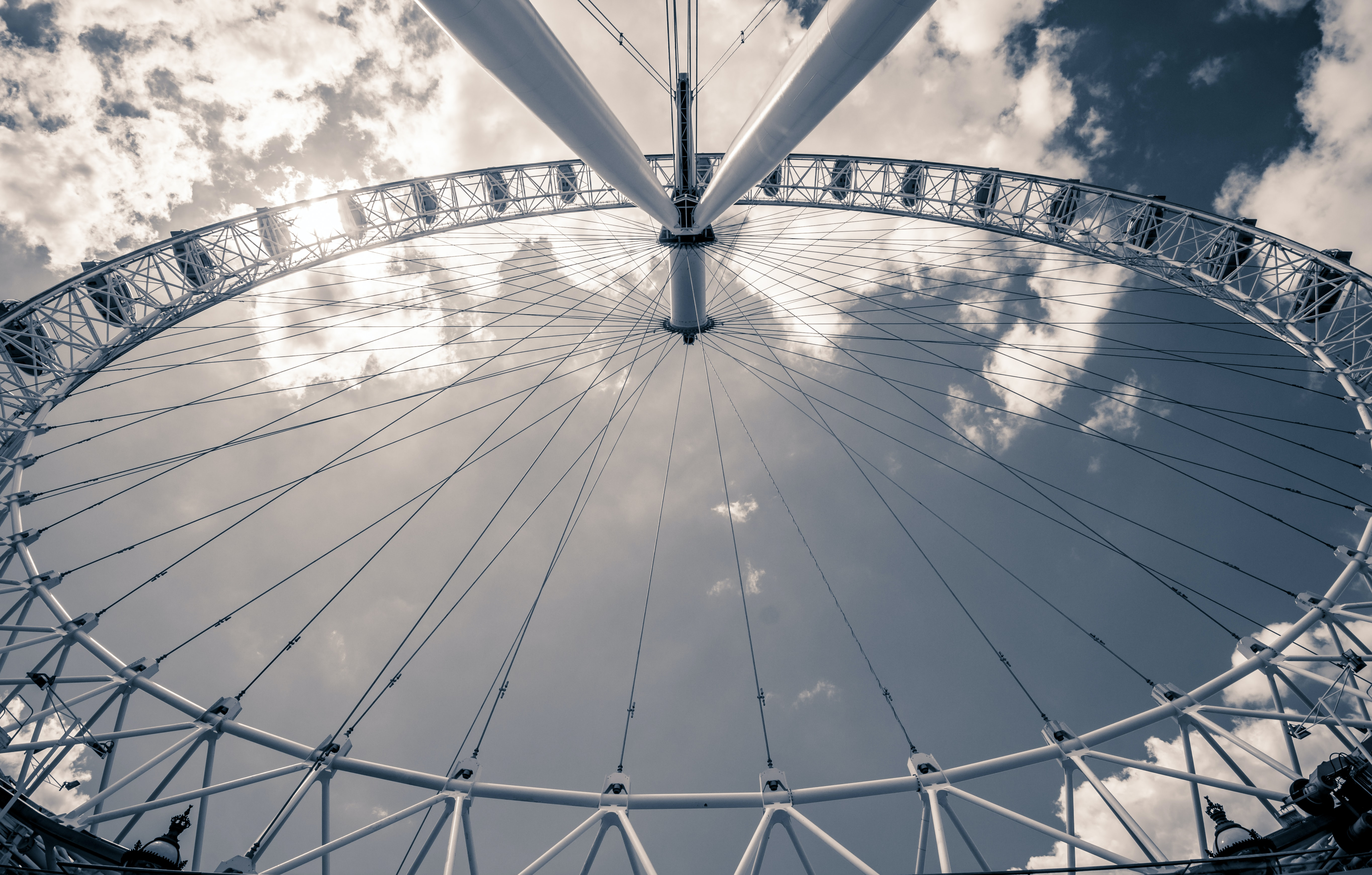 A Ferris wheel seen against a blue sky with fluffy clouds