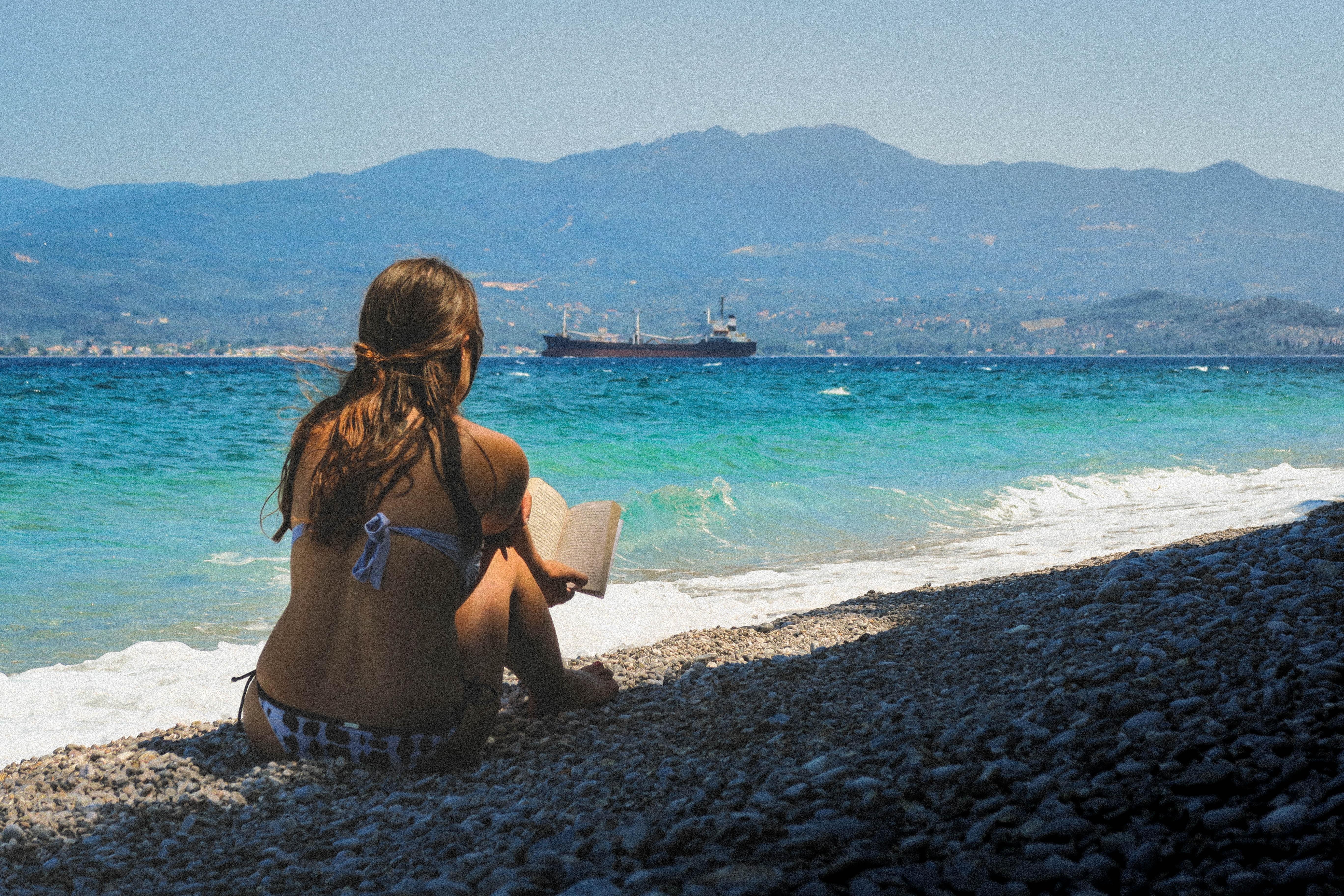 Woman in a bikini sitting on a pebble beach reading a book at Glifa