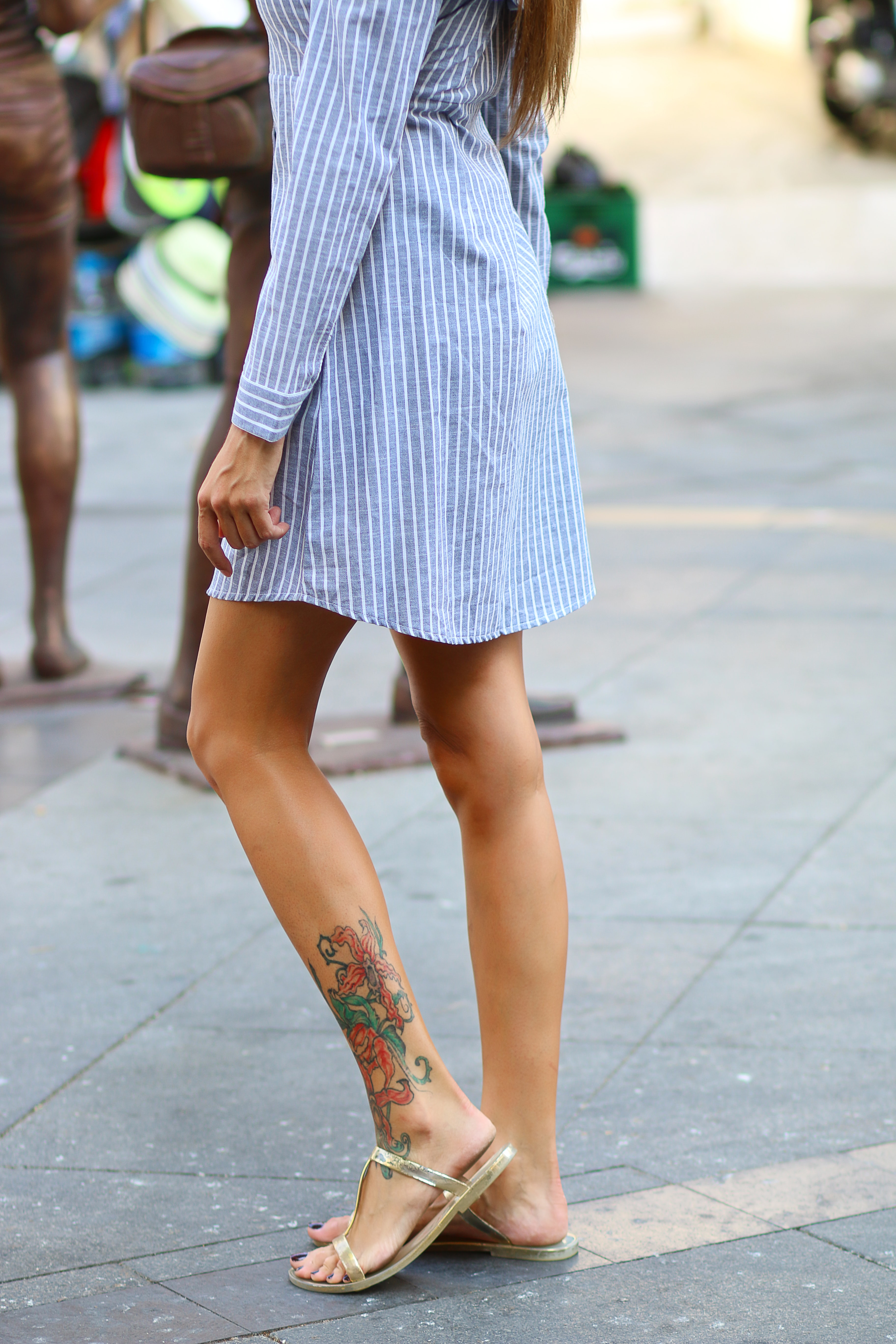 Low shot of a woman with an ornate ankle tattoo outside