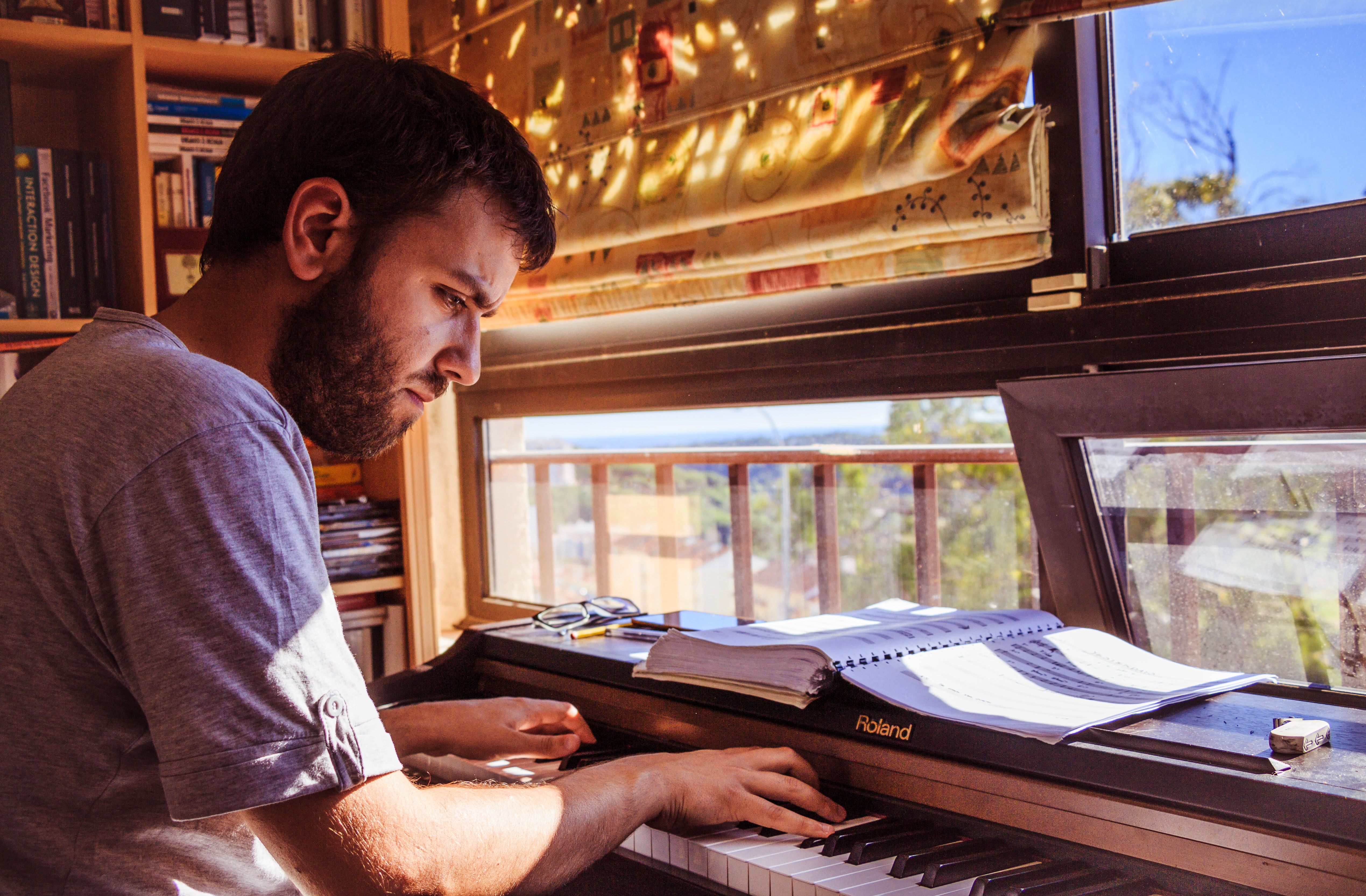 A bearded man plays the Roland piano intensely by the windows with the outdoors in view.