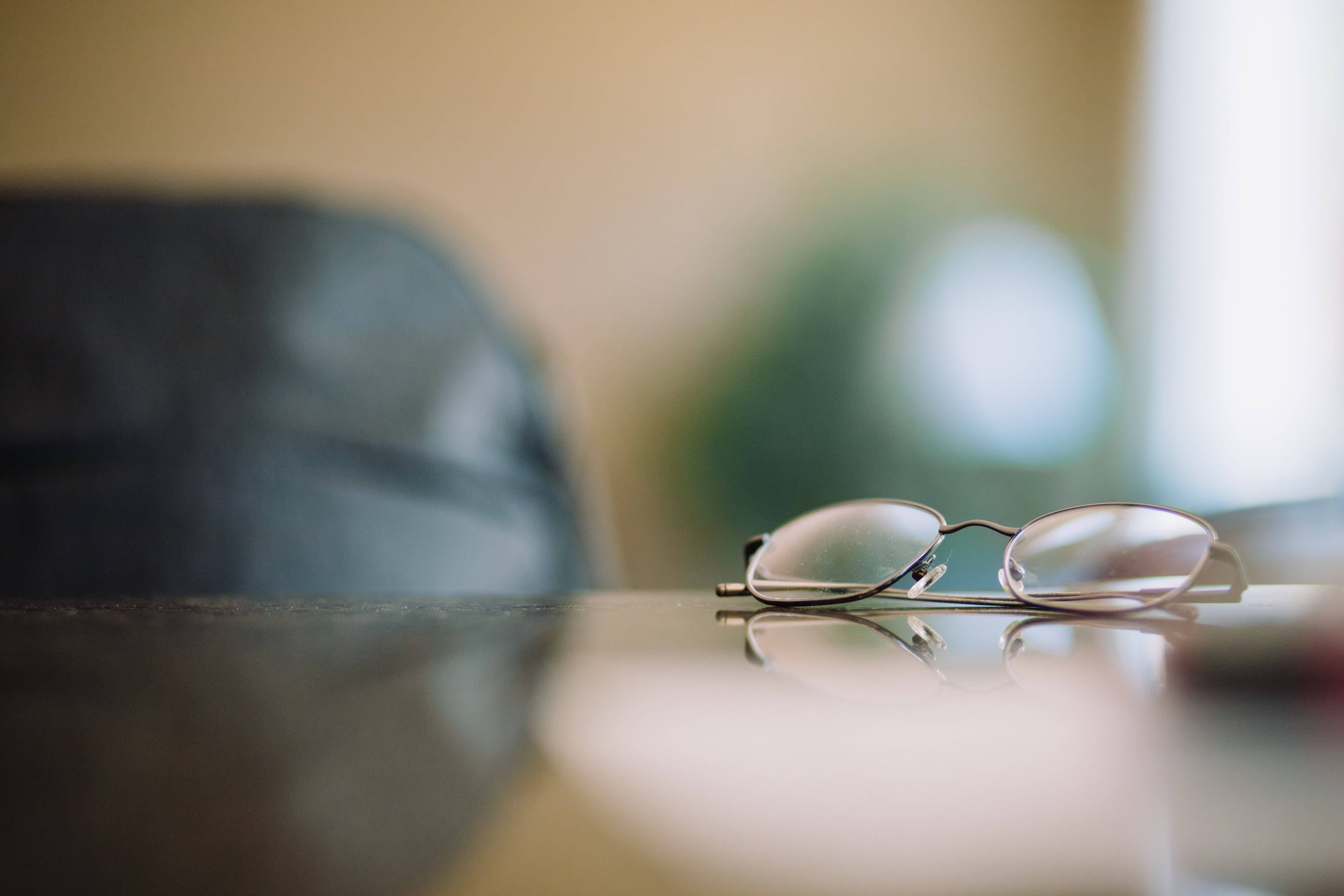 Close-up of a pair of glasses on a glossy surface