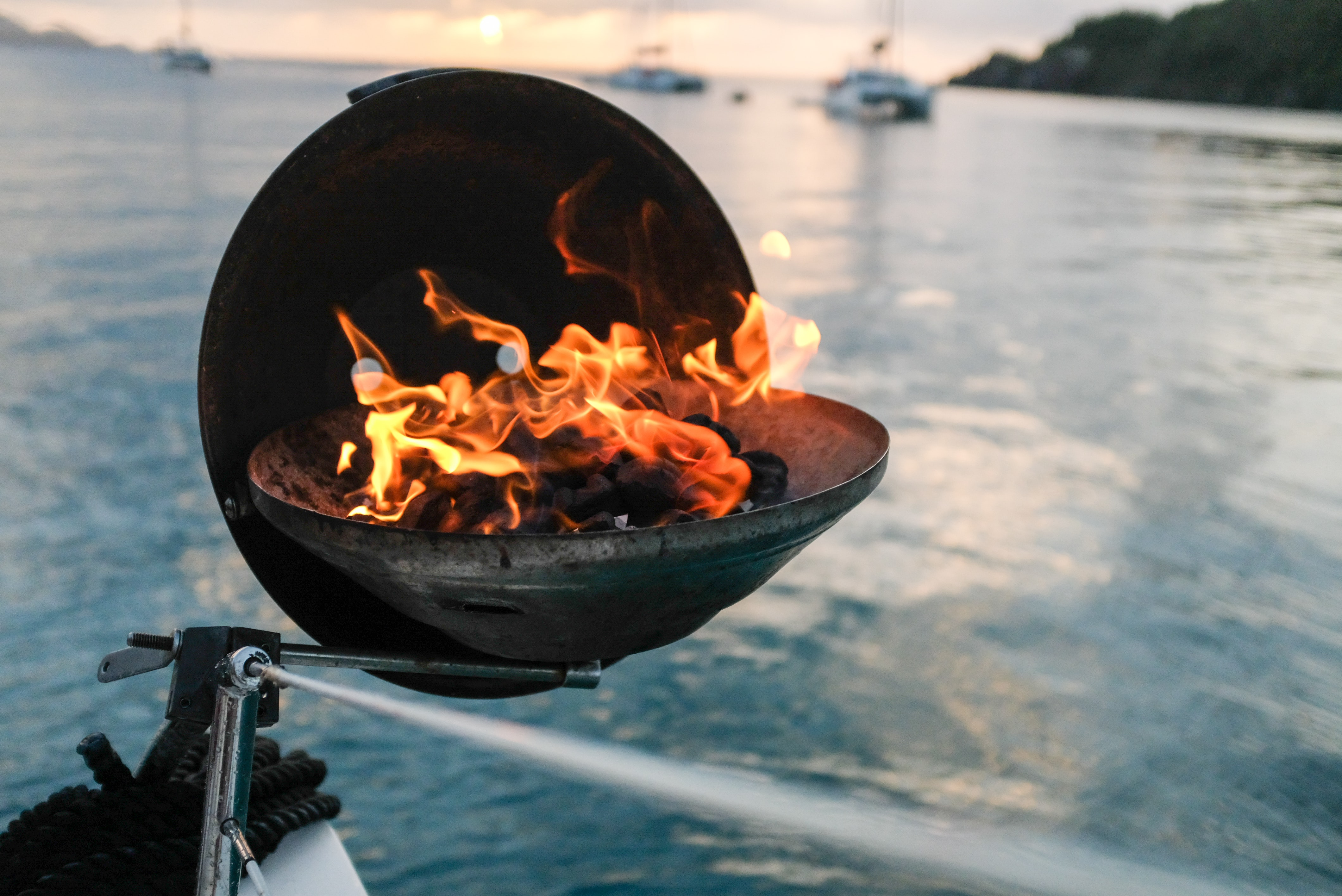 round black fire pit with charcoal on it burning beside calm body of water
