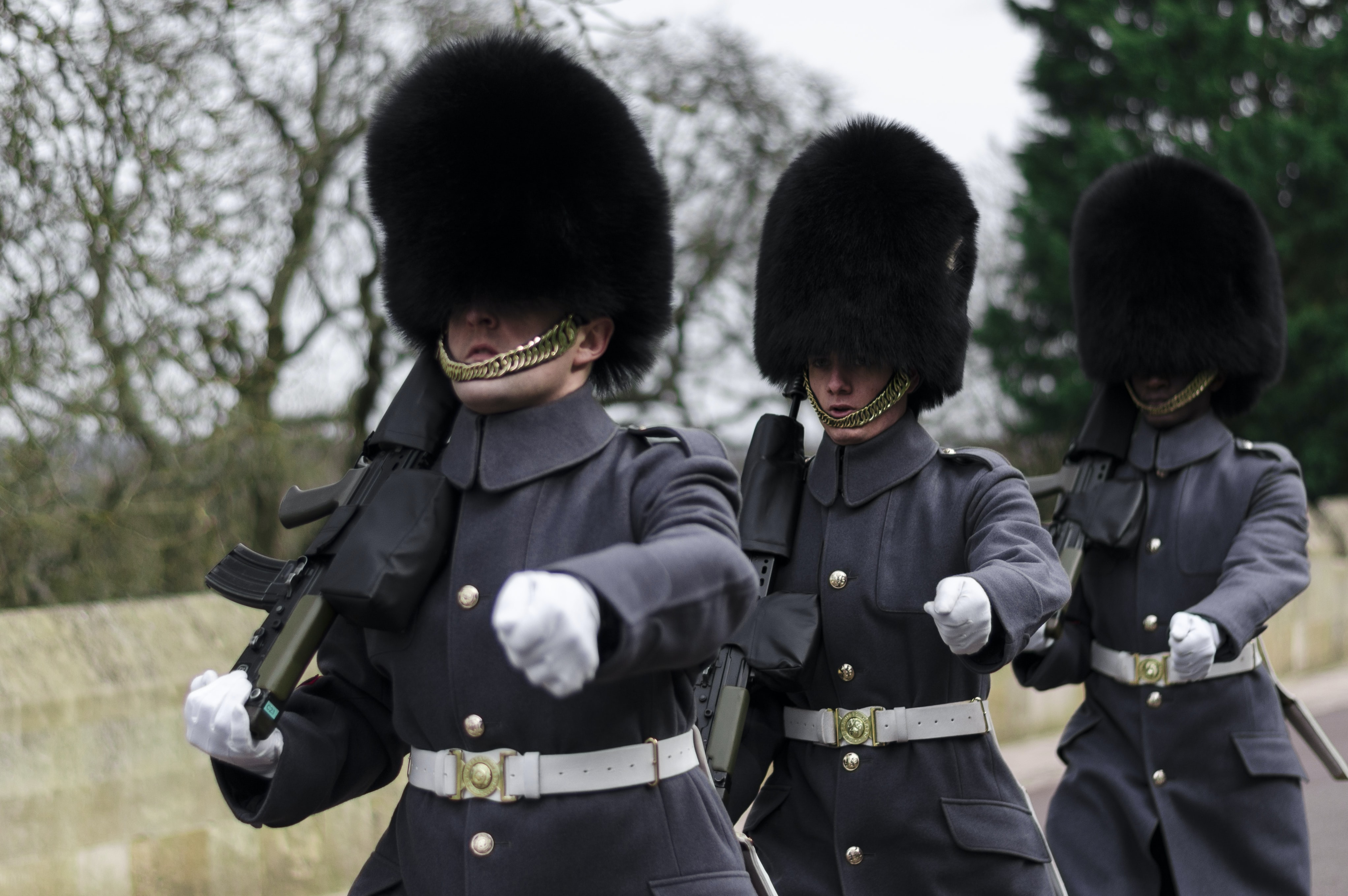 A group of queen's guard men in dark uniforms holding rifles marching in formation