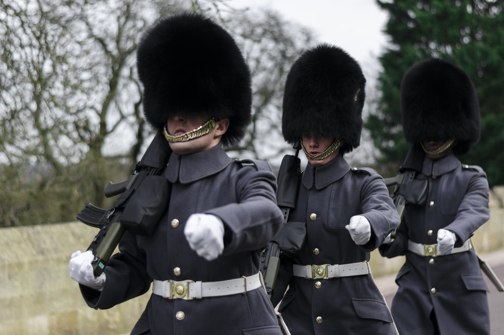 three Queen's guards carrying sub-machine guns