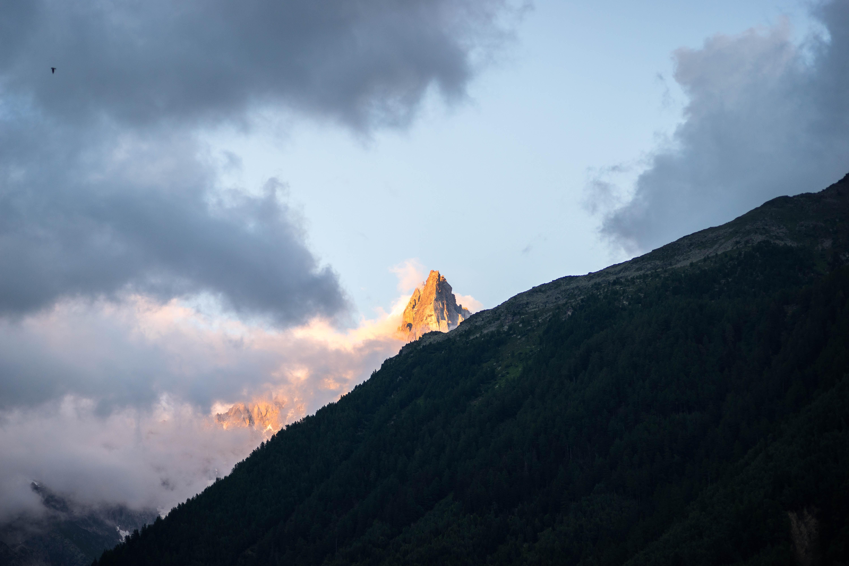 Sunlit mountain peak behind clouds in Chamonix