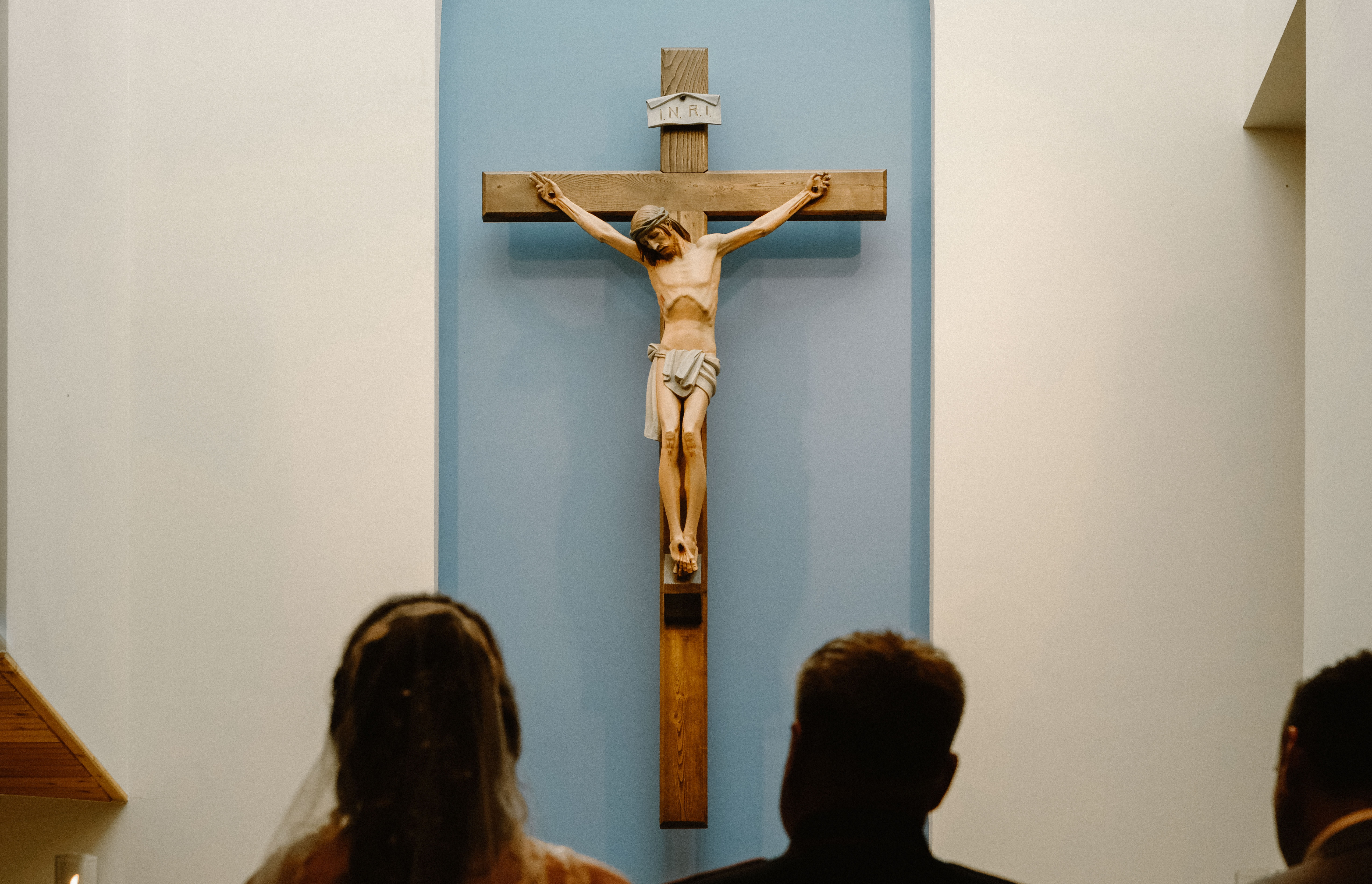 three people staring at the crucifix