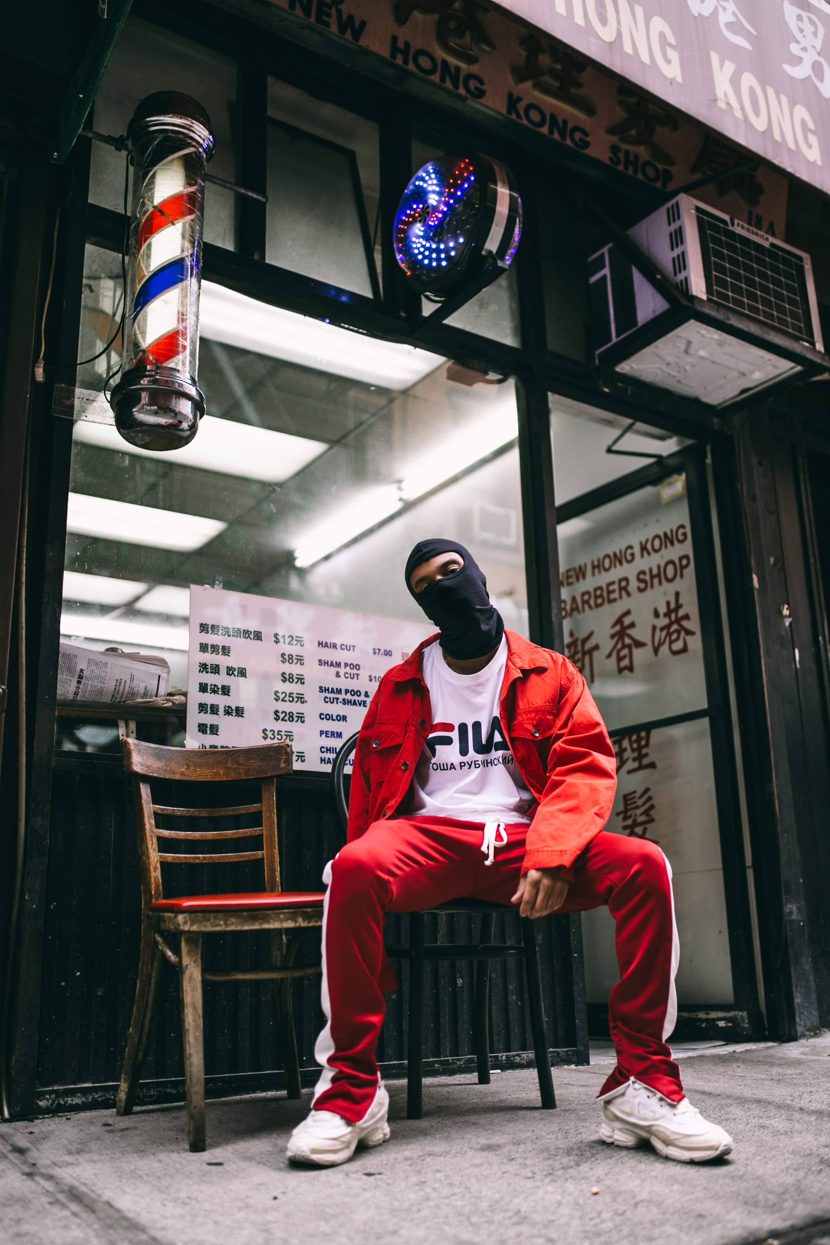 A nan in a balaclava and Fila sportswear sits in front of an old barbershop.