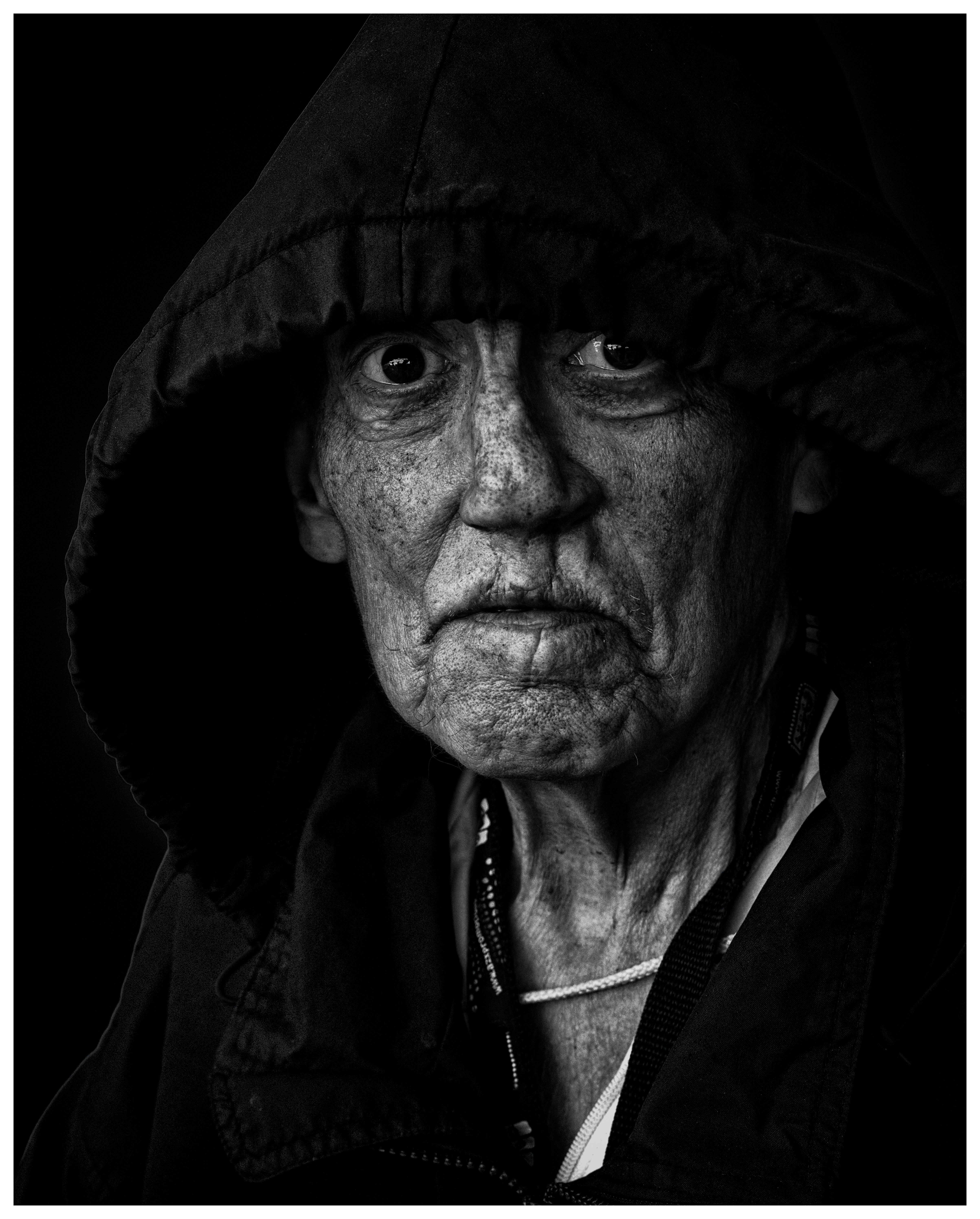 Black and white shot of elderly woman with wrinkles and hood, Milwaukee