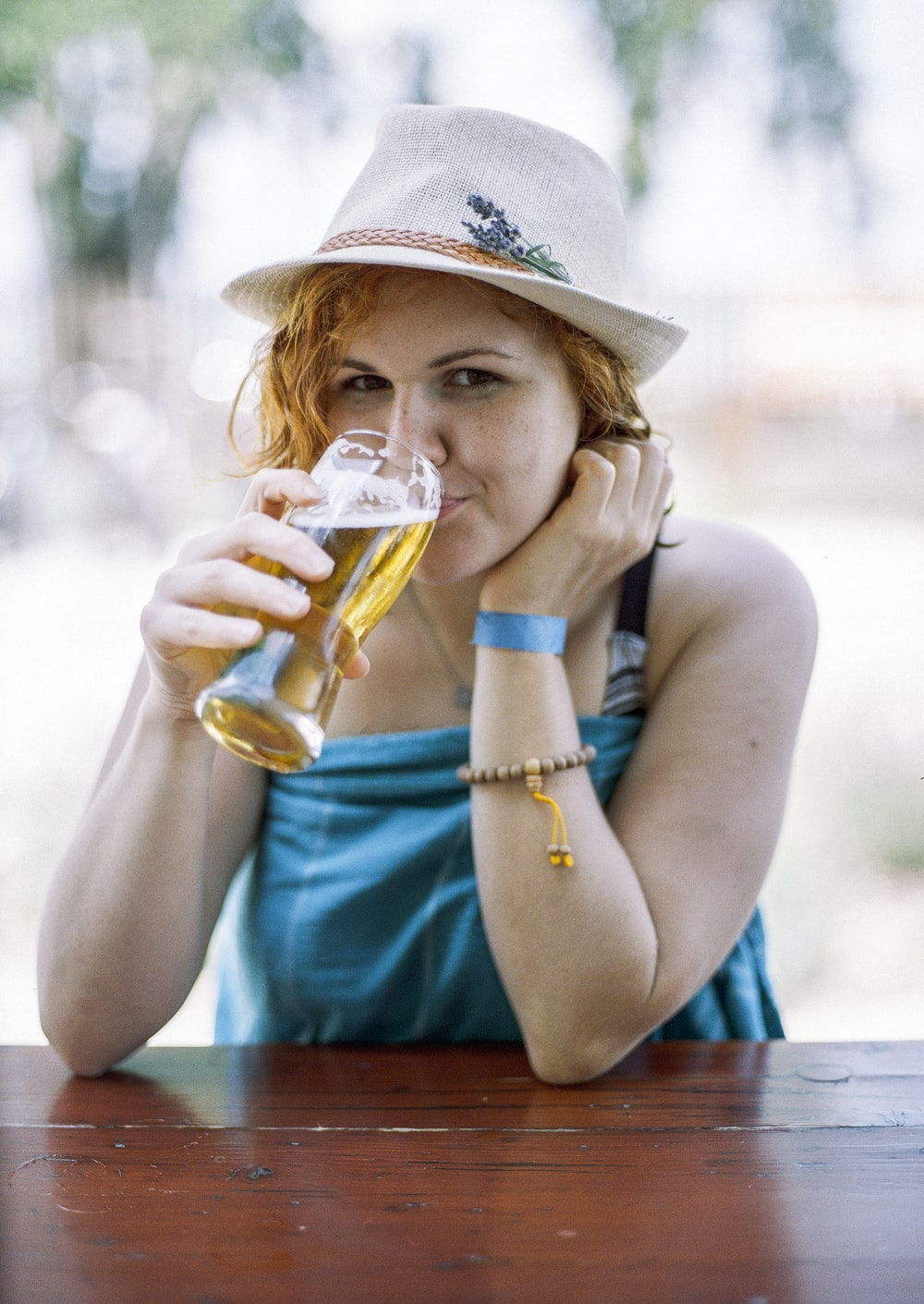 woman drinking glass of beer during daytime