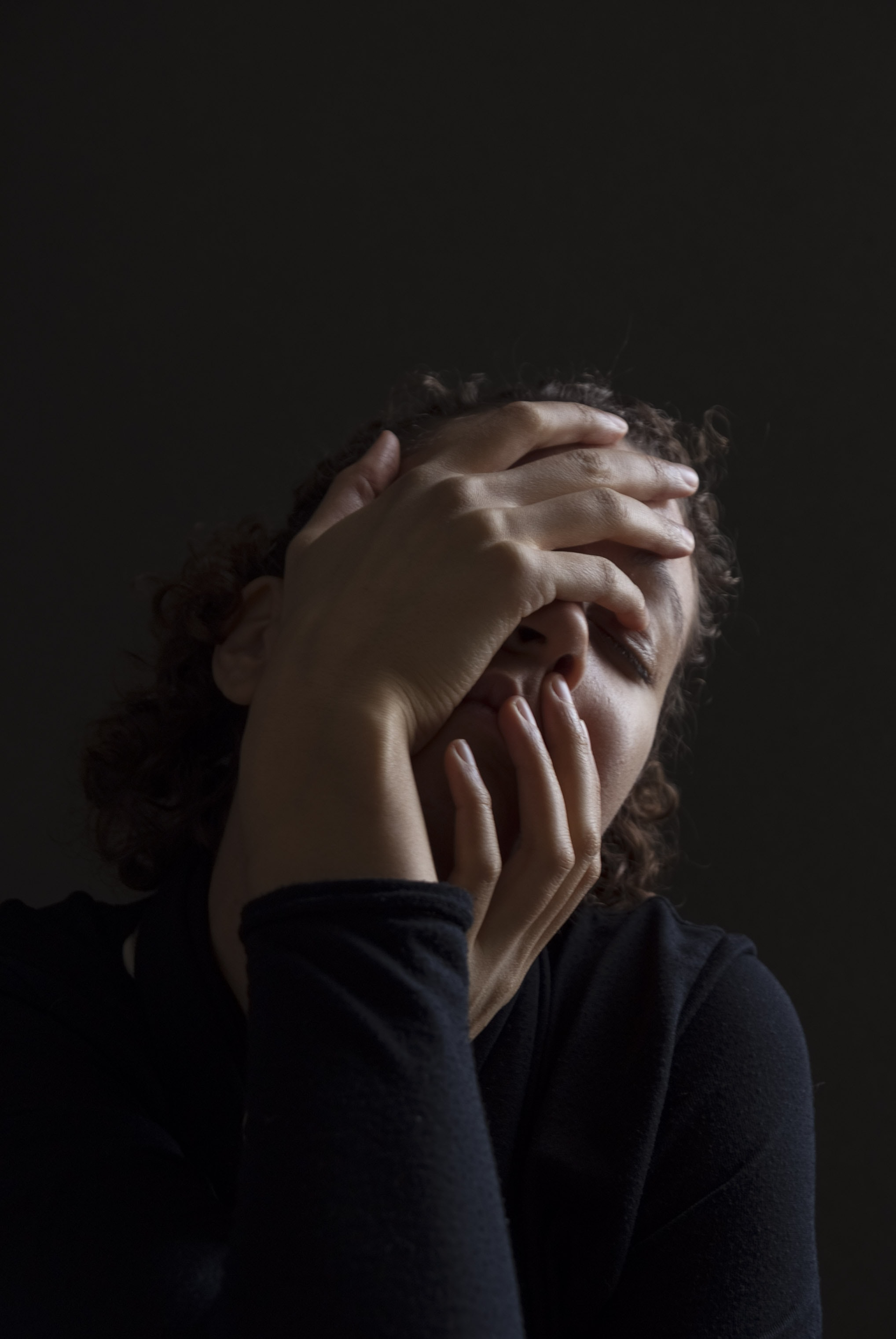A woman in black against a black background holds both hands over her face