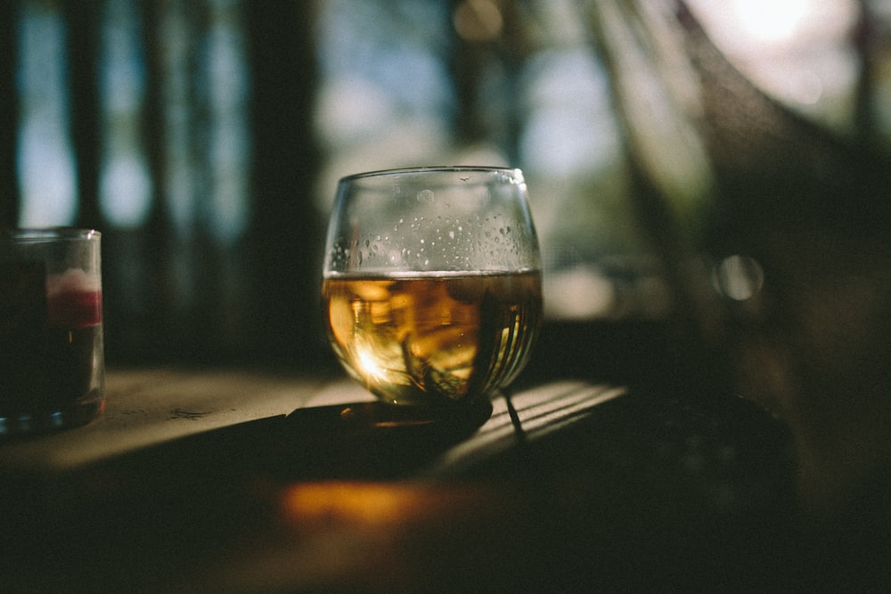 clear snifter glass on brown wooden table