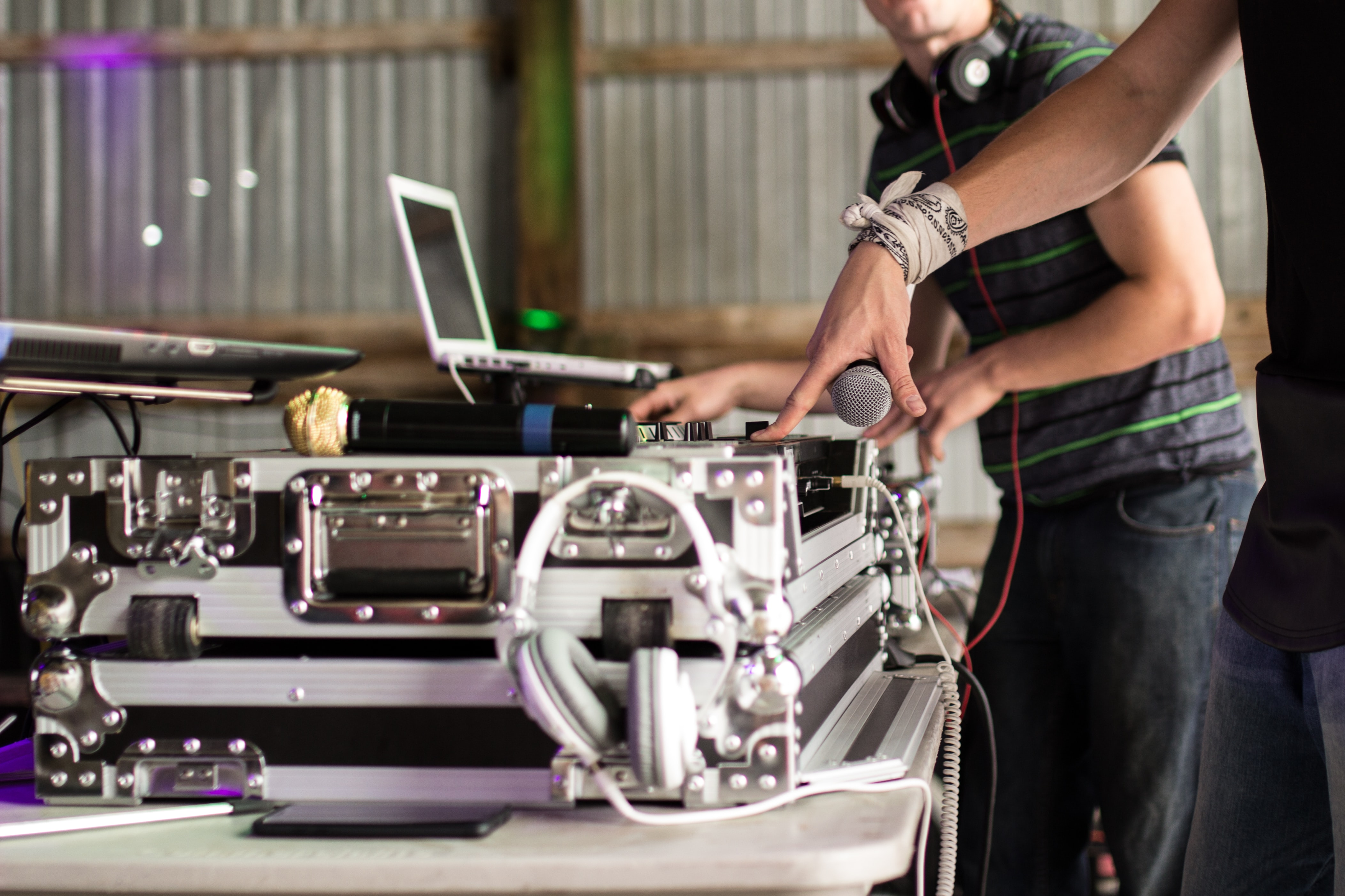 A DJ with a bandana wrapped around his wrist mixing on a turntable and mixer beside two laptops, a microphone, white headphones, a smartphone, and another DJ wearing beats headphones