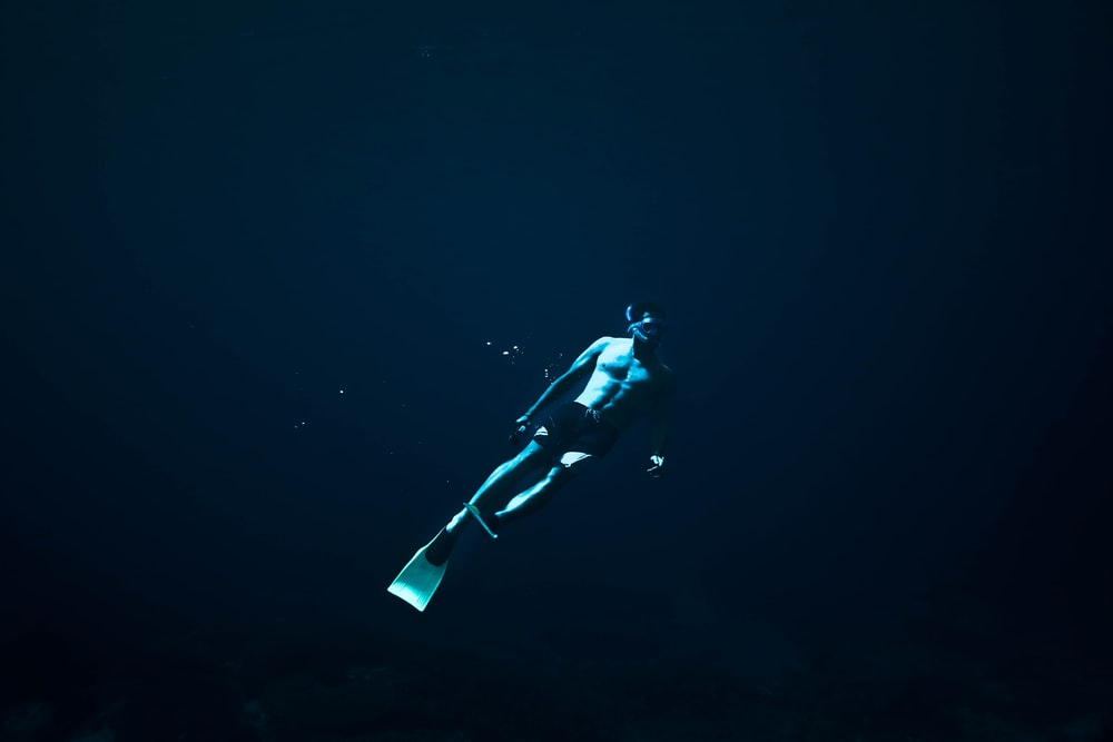 man diving underwater photo