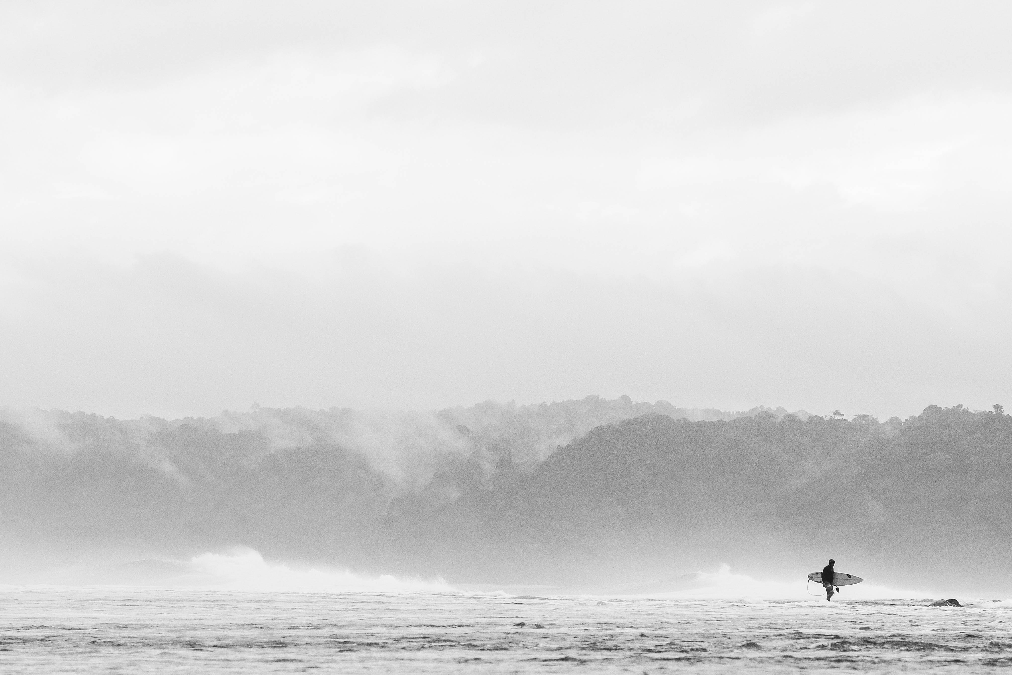 person carrying surfboard standing on the water during daytime photography