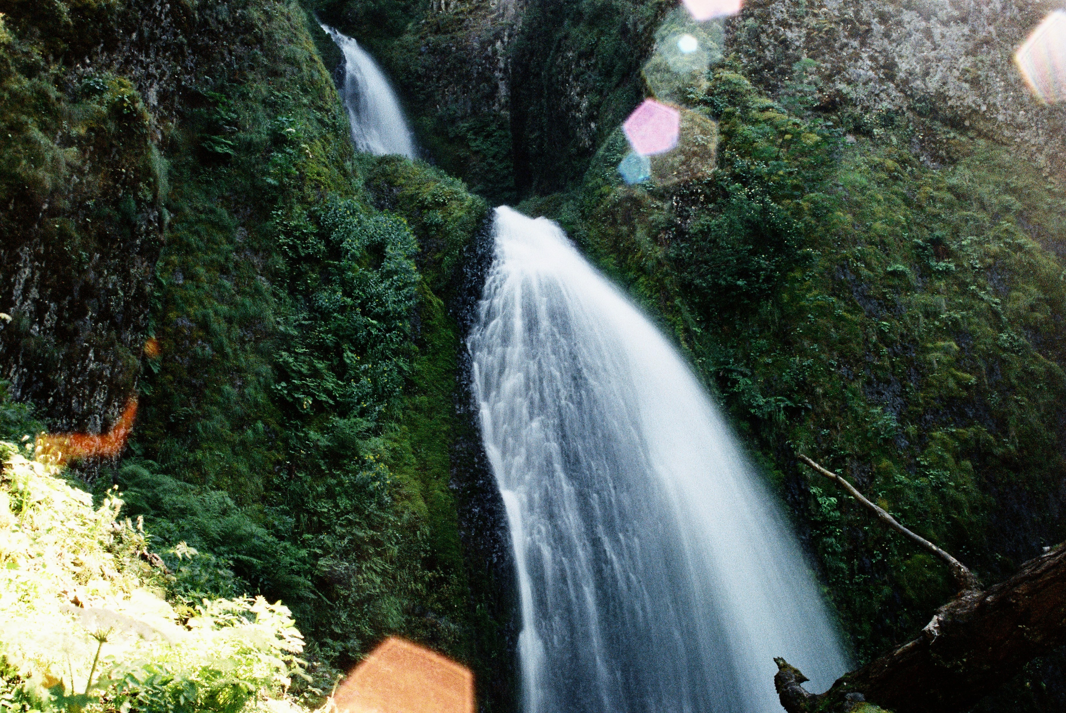 waterfalls in between mountain covered with green plant s