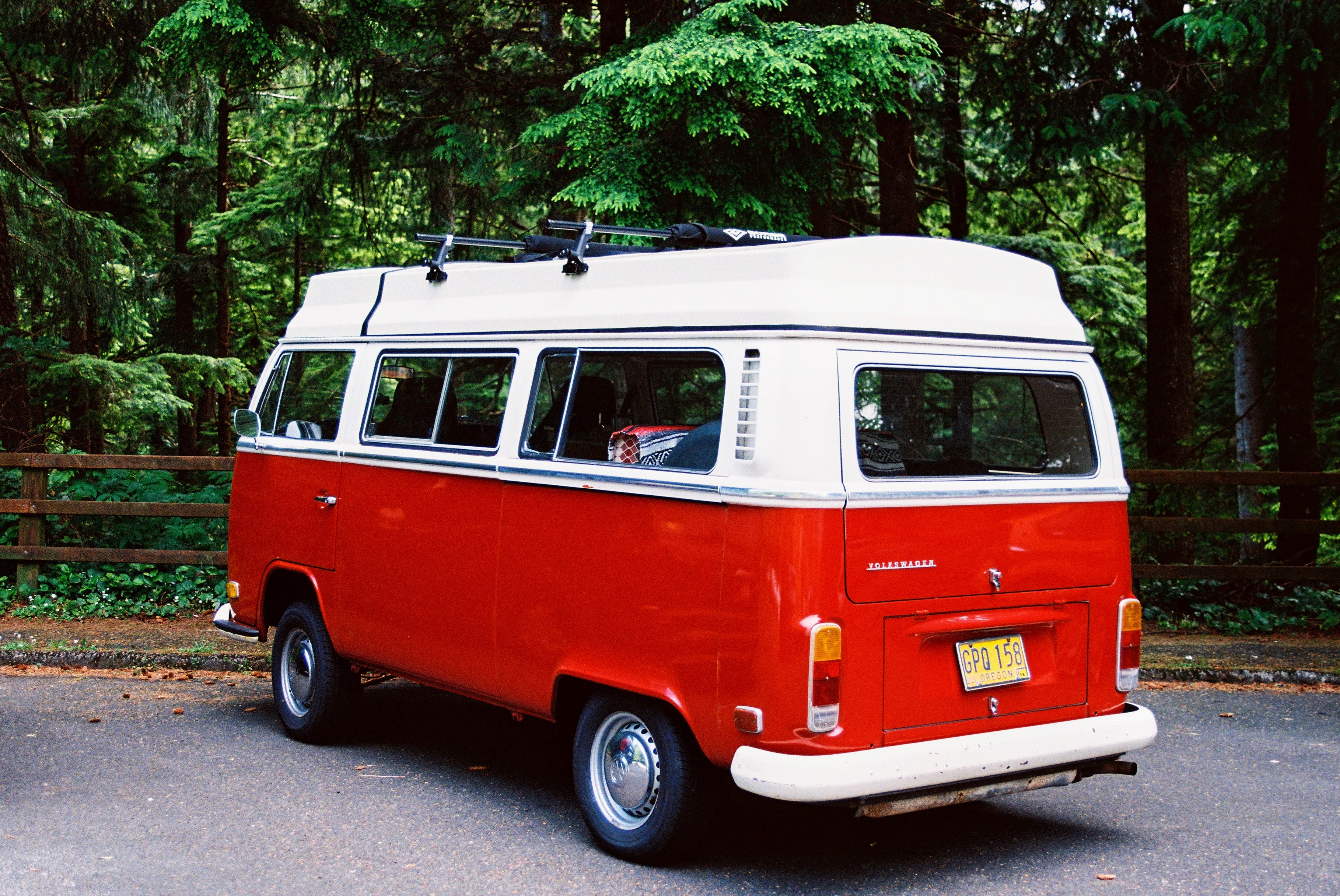 A red vintage Volkswagen camper van parked near a forest