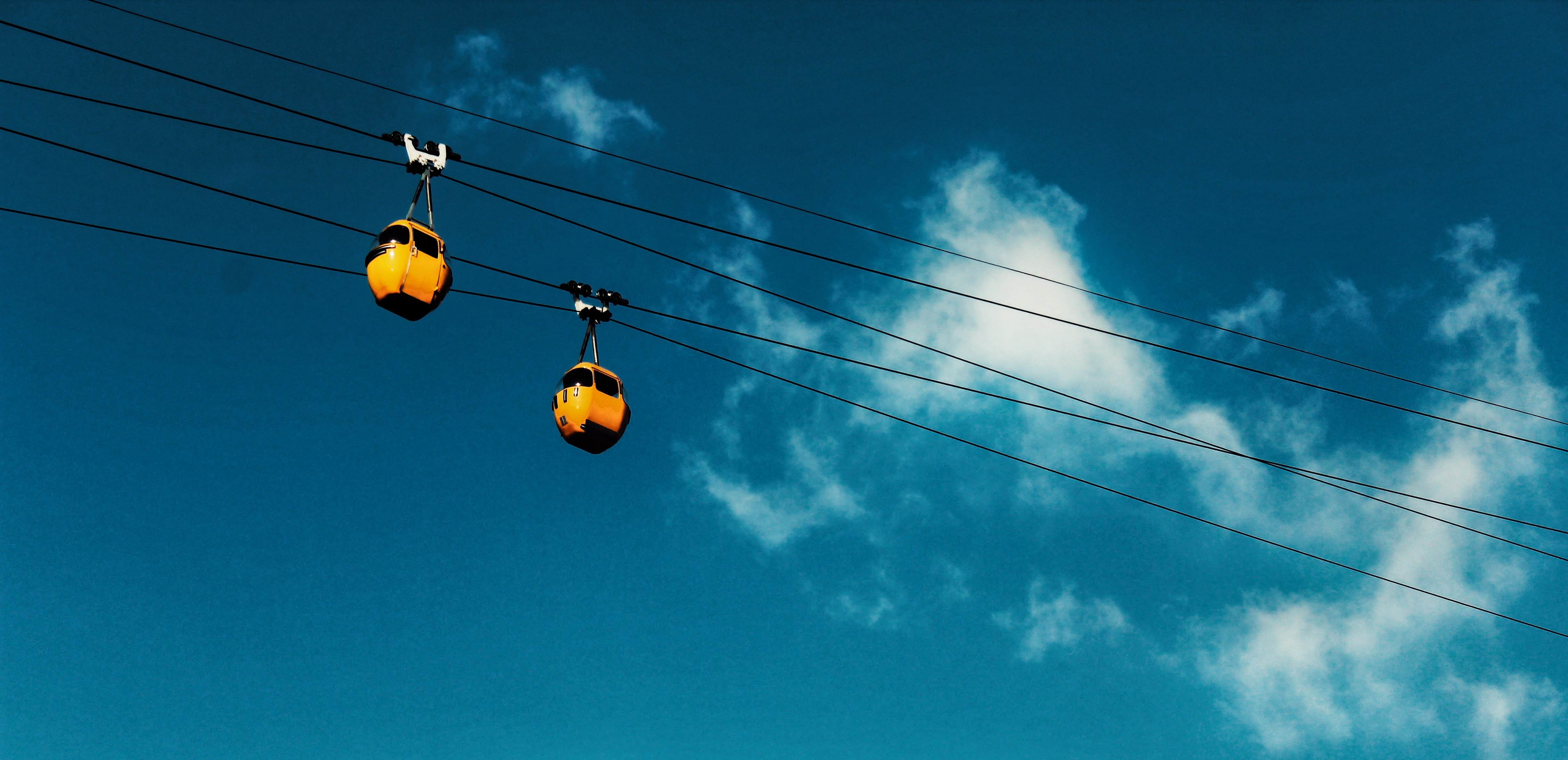 Yellow cable cars ride on wires against a blue sky