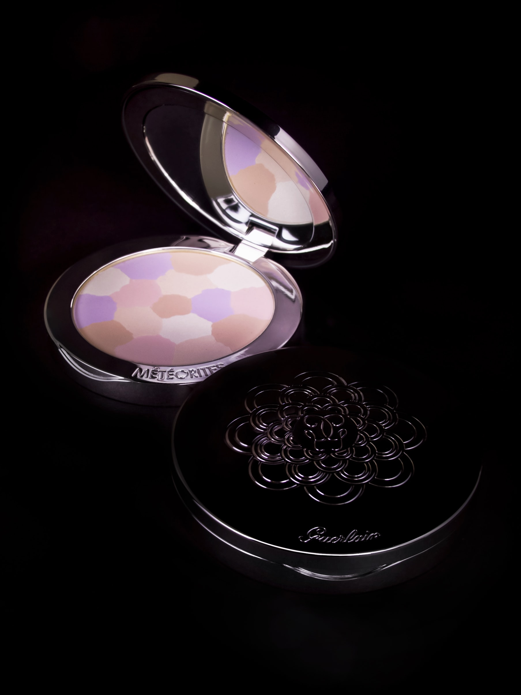 Two compact powder cases are placed against a dark background.