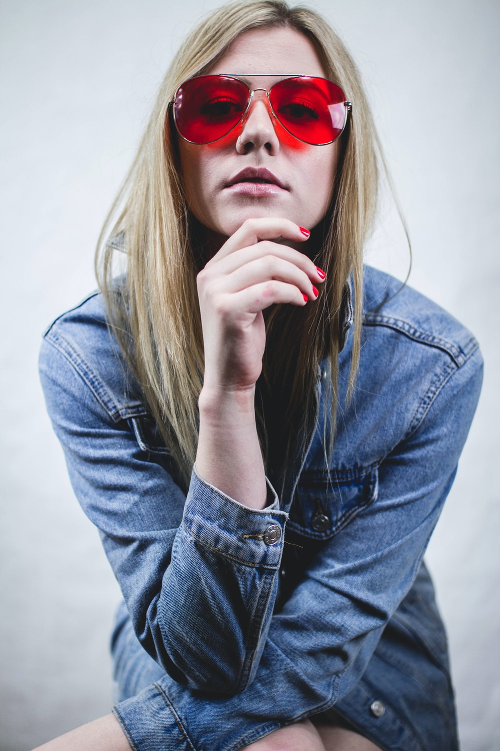 woman in blue denim jacket wearing red sunglasses and red manicure with hands on chin