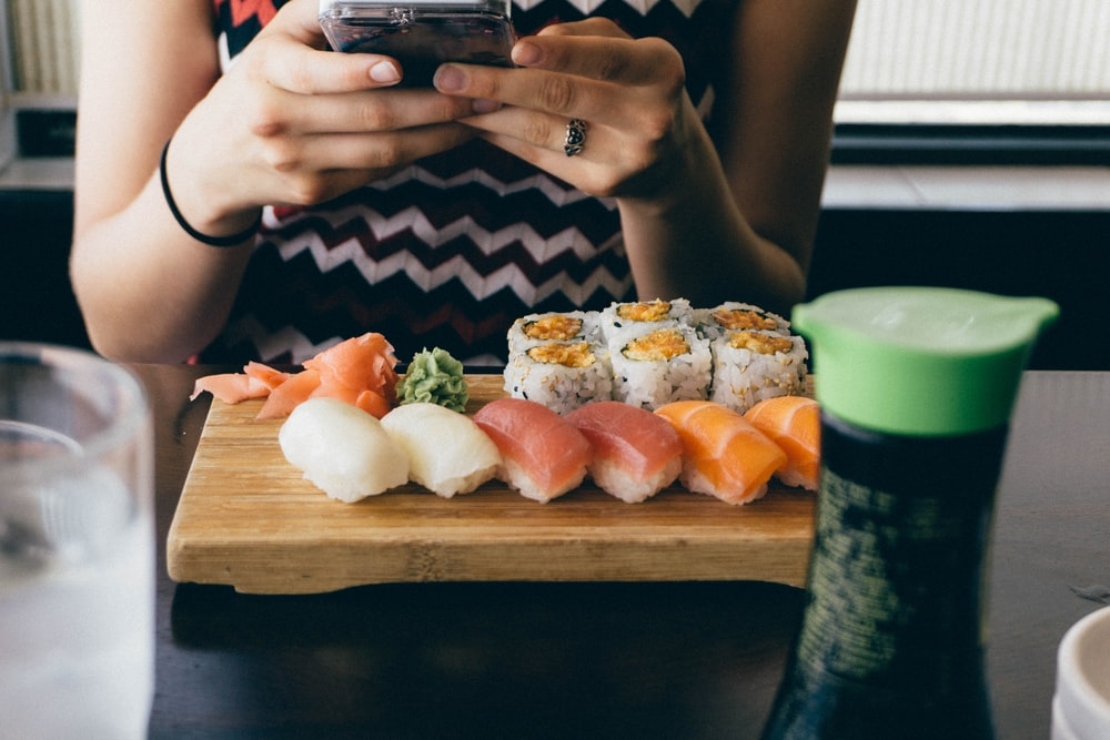 person sitting in front of sushi dish on table