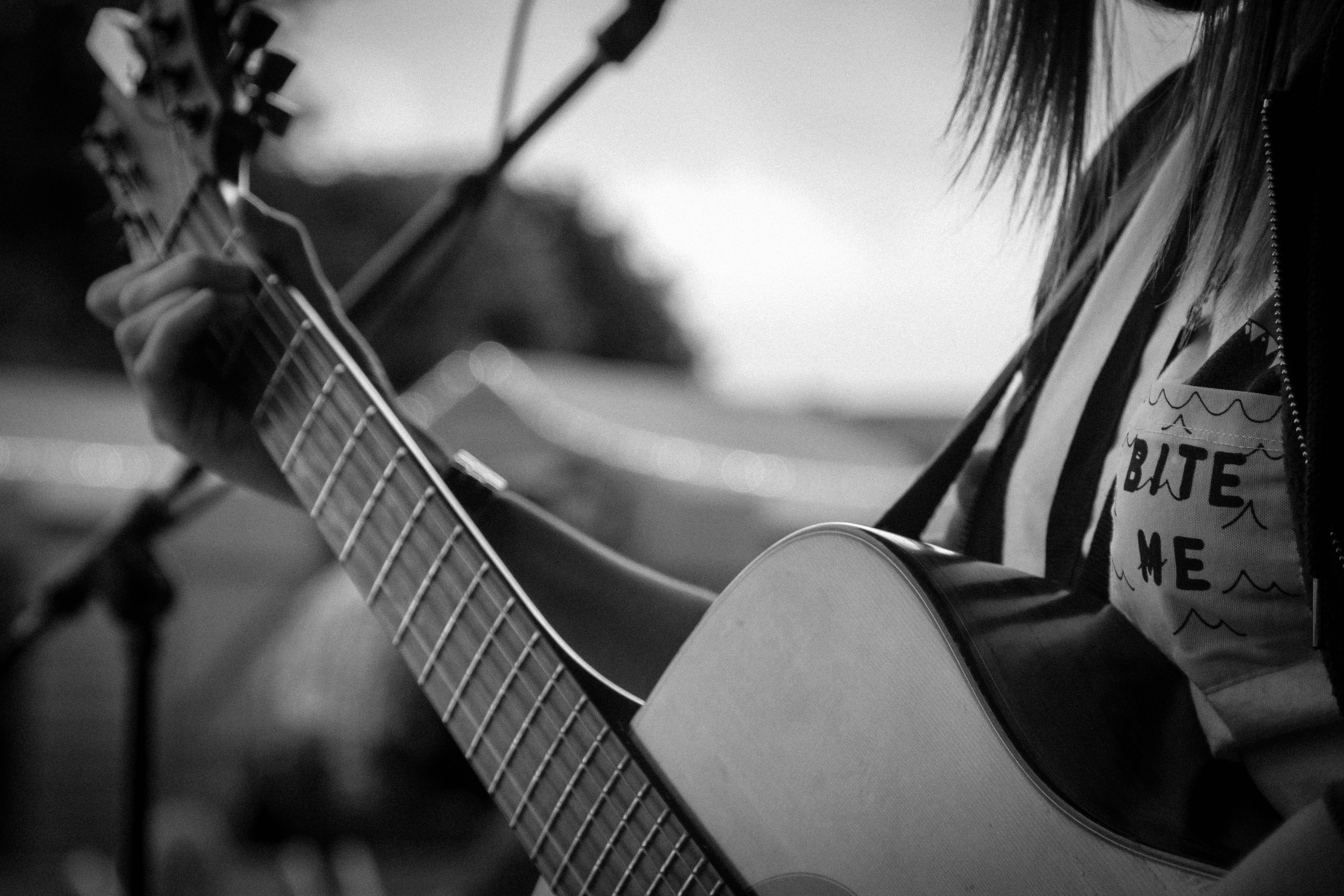 Black and white close up shot of person playing guitar with microphone, England