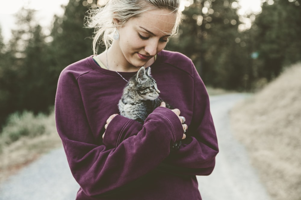 selective focus photography of woman hugging gray kitten