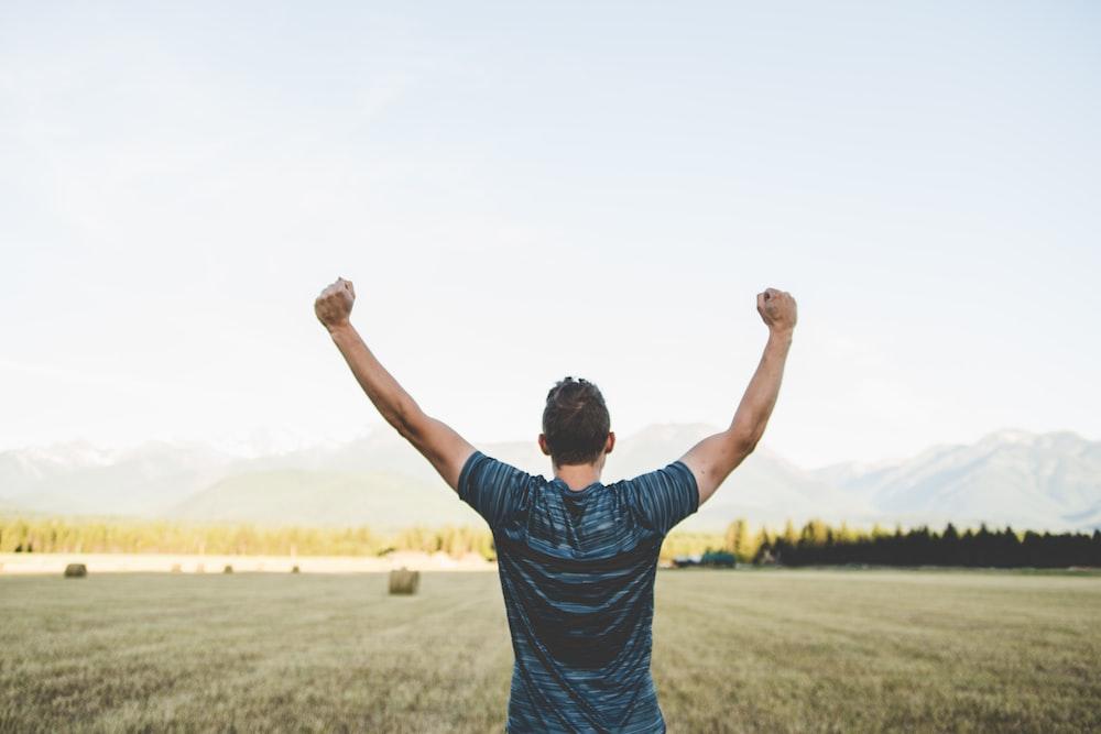 man reaching hands up high taken at daytime