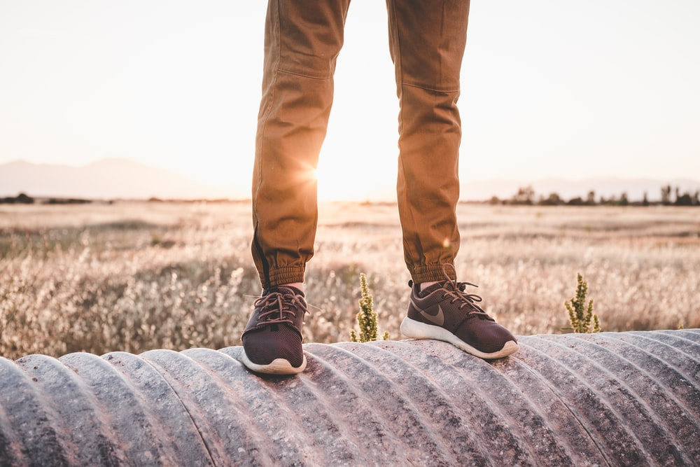 filtered photography of man wearing Nike shoes standing at threaded drum with scenery at back