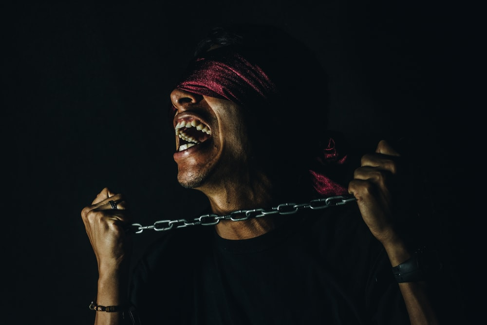 man with chain and blind fold