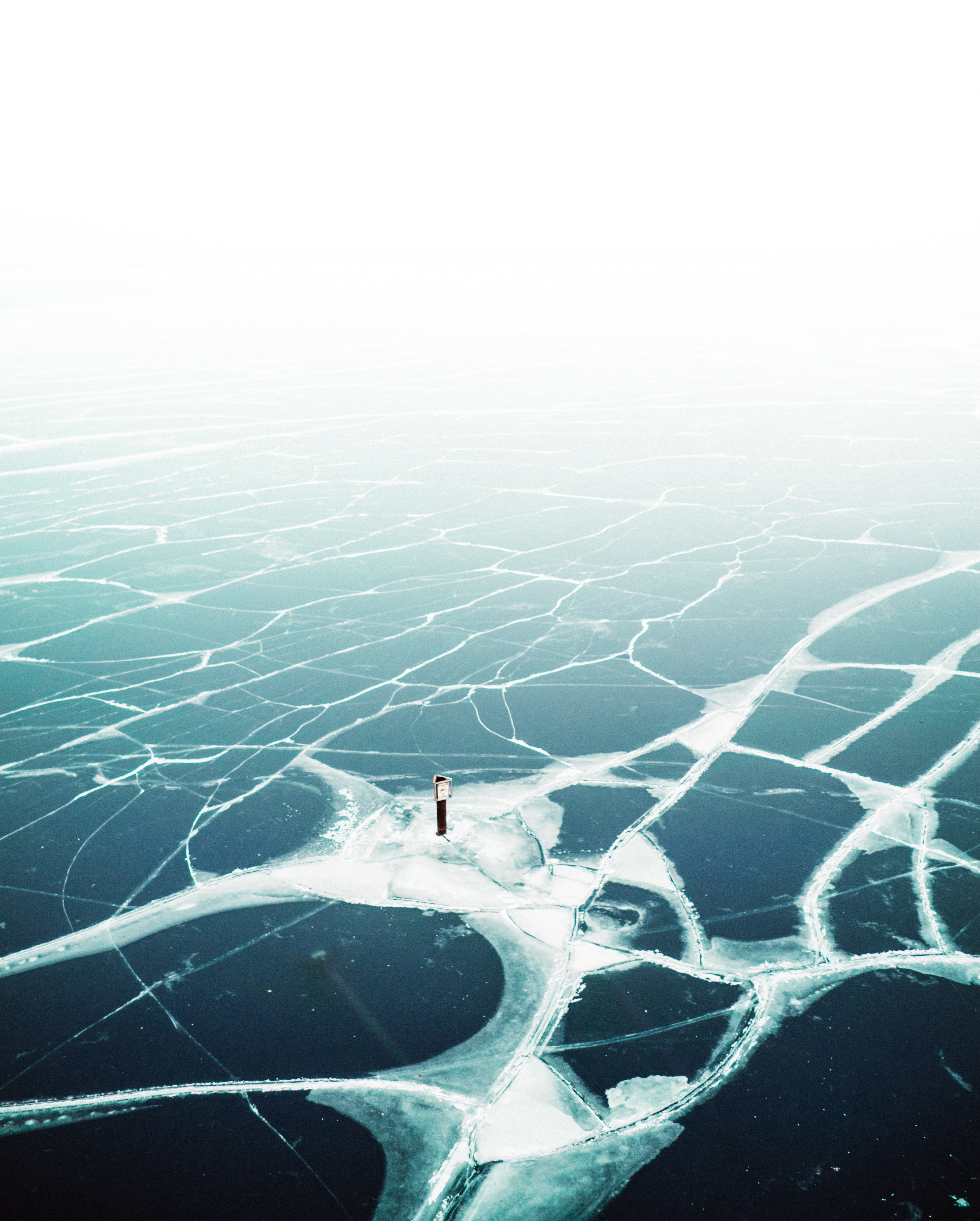The ice on Lake Michigan cracks, creating a contrast of dark and light