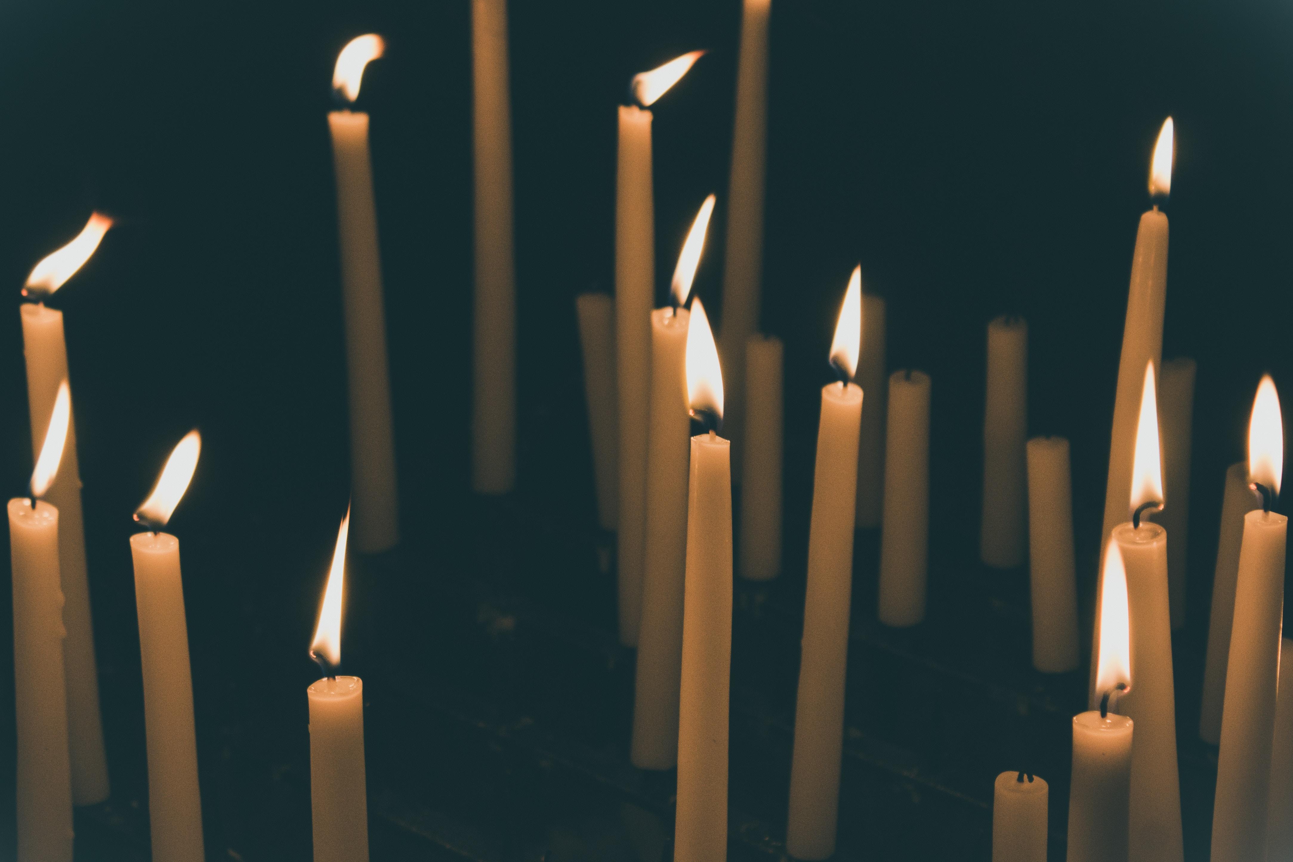Tall candlesticks burning besides shorter unlit candlesticks in the dark