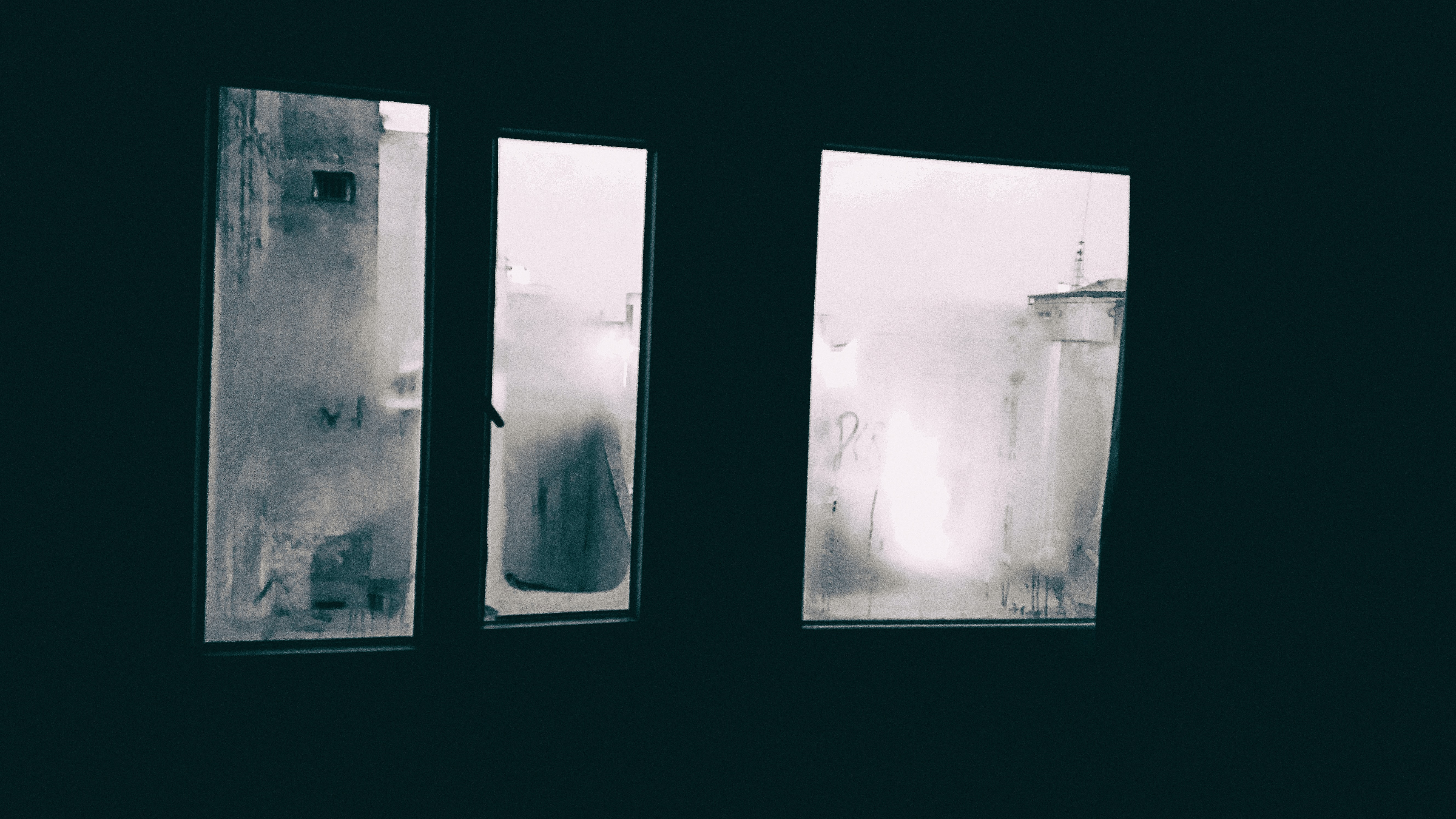 Dark room interior looking out through foggy window in the winter at the buildings outside