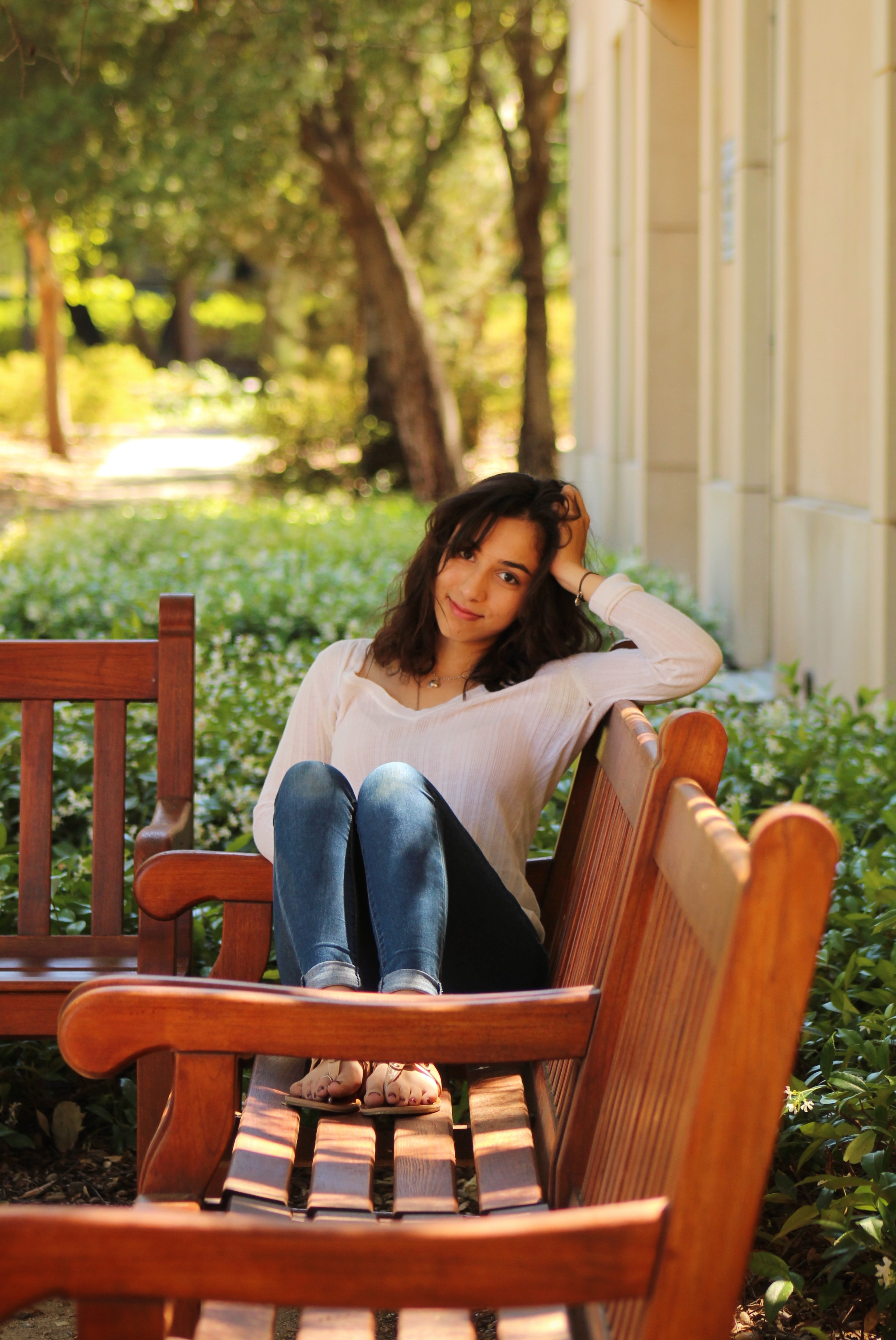 Portrait of a woman smiling on a bench on the Stanford campus with her knees up