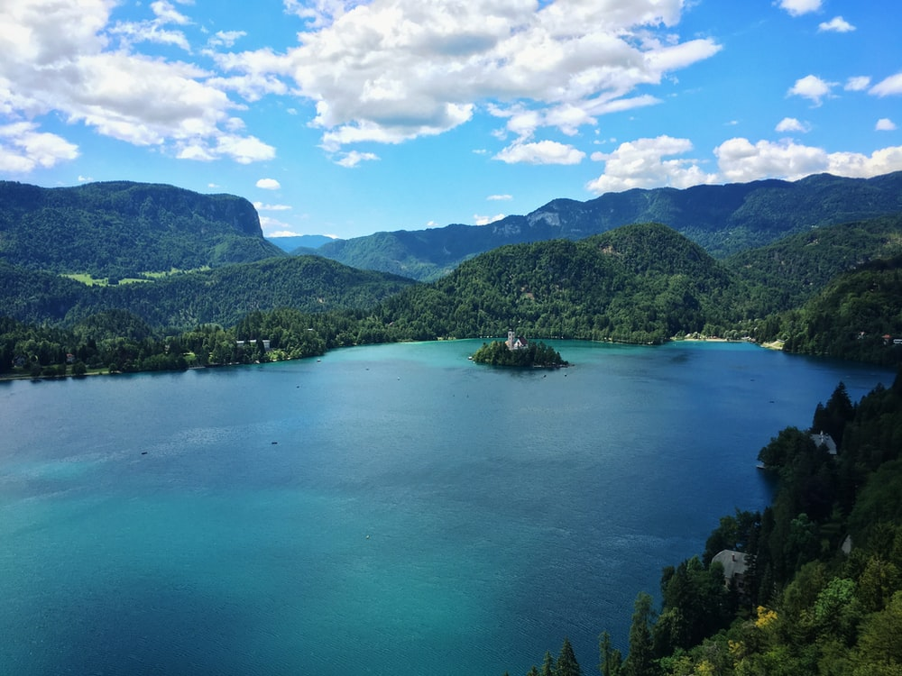 turquoise and azur body of water surrounded by mountain range and forest under white clouds and blue sky at daytime