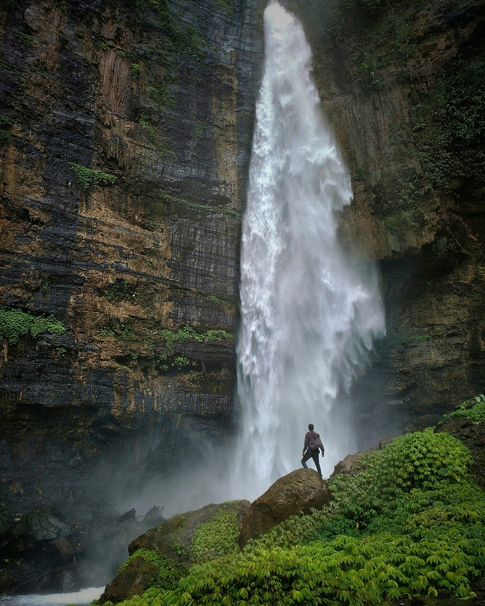 person standing on brown rock formation looking at waterfalls during daytime