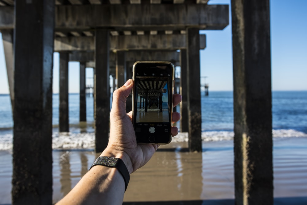 person holding black smartphone taking photo of sea during daytime