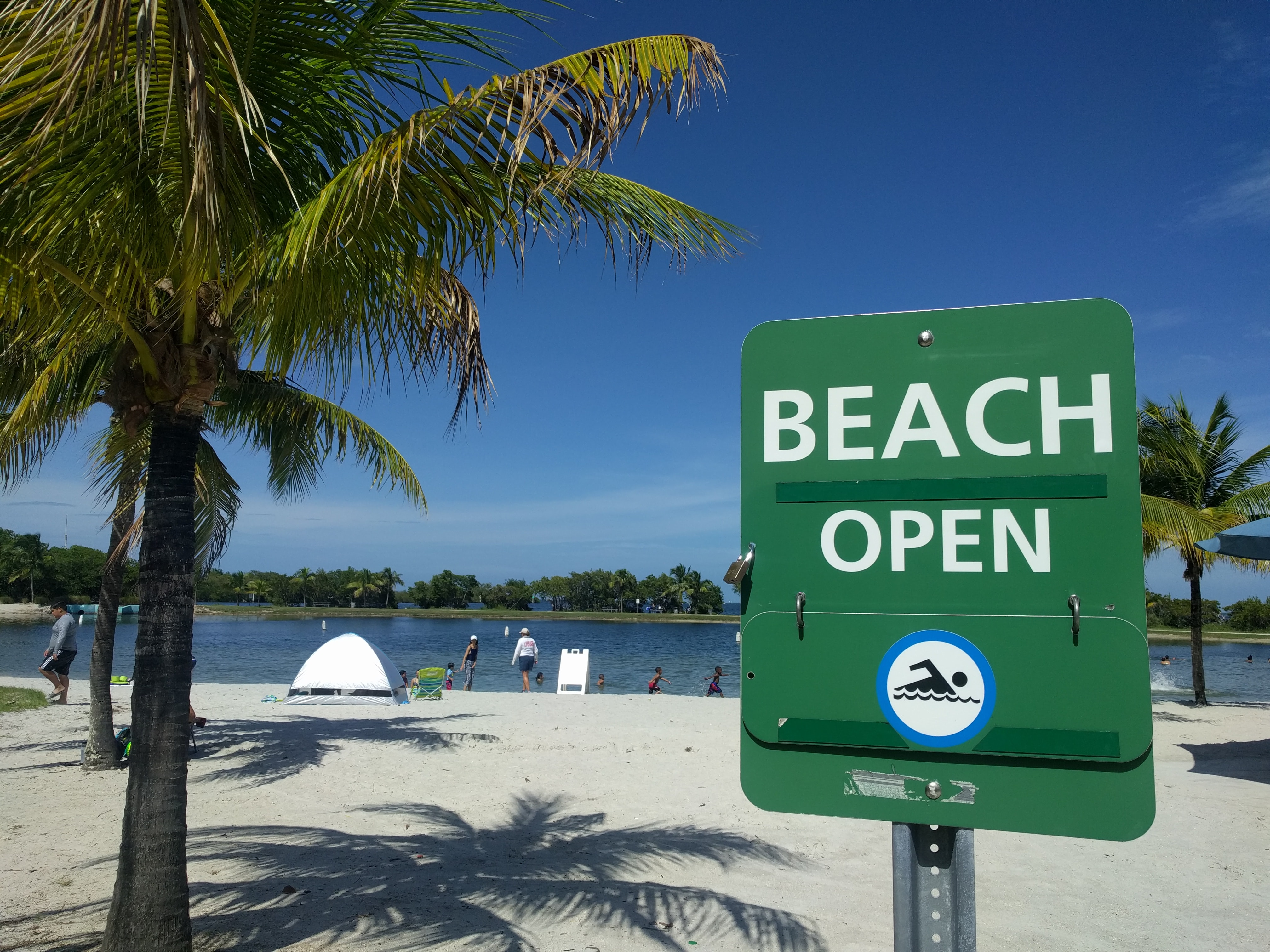 Green Beach Open sign at the sand beach in Homestead, Florida
