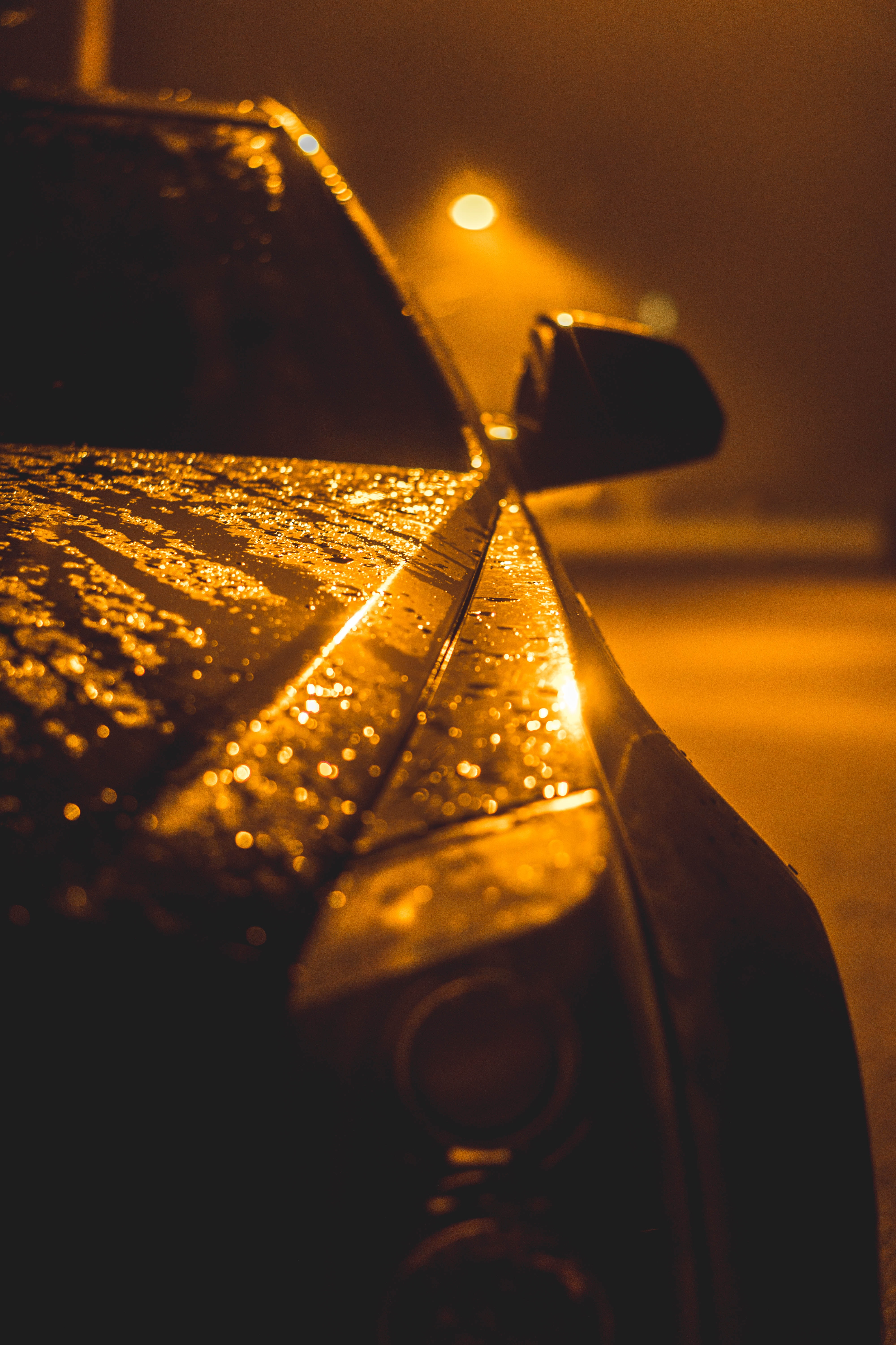 The engine bonnet of a car soaked in rain.