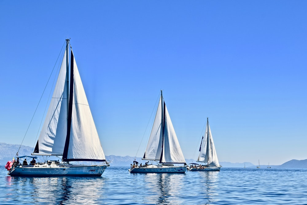 three sail boats on water during daytime