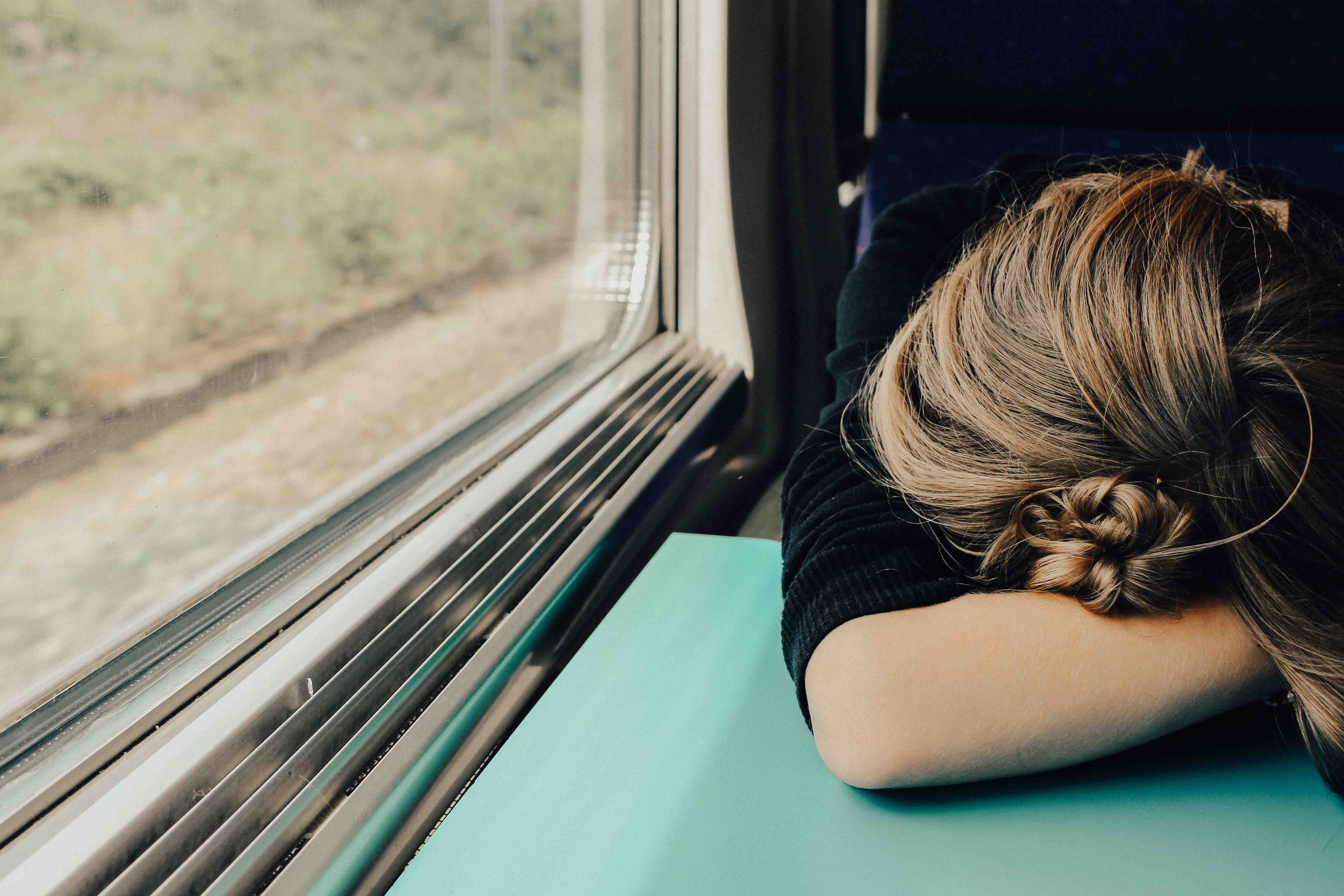 Tired woman with her head down on a train tray table